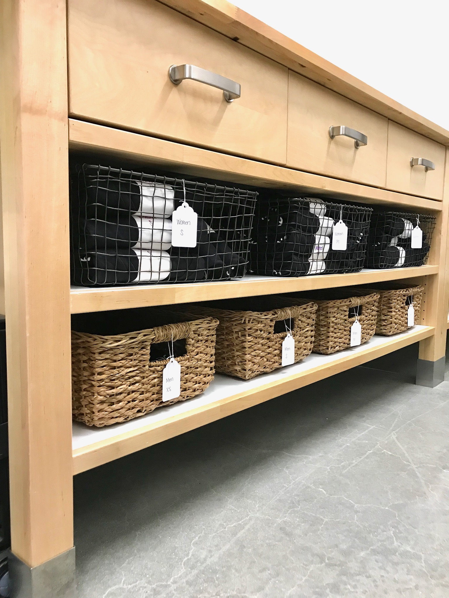 Labeled wire and wicker baskets used on wooden shelving to organize merchandise for a local small business.