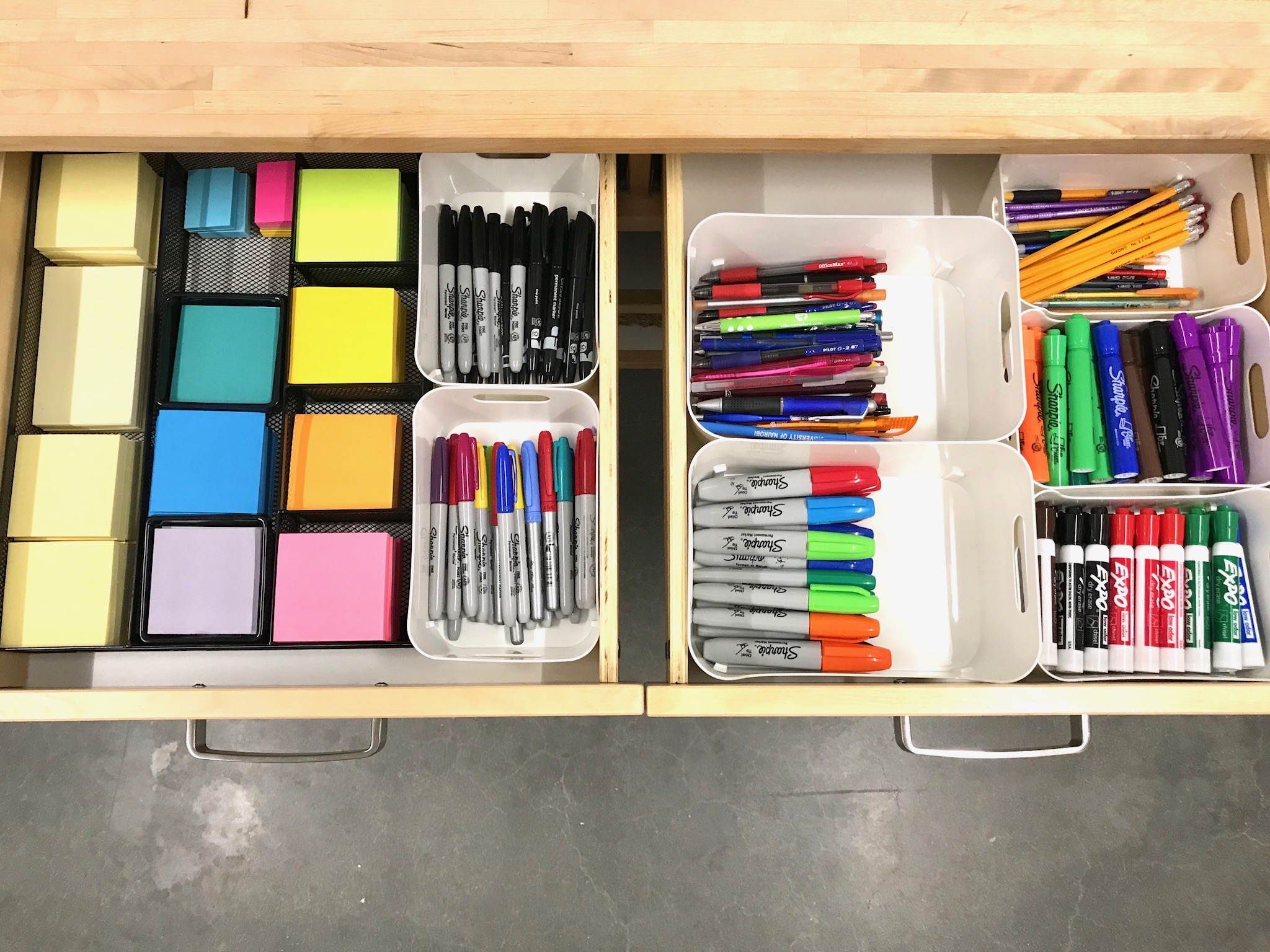 Organized office supply drawers with markers, pens, and post-it notes.