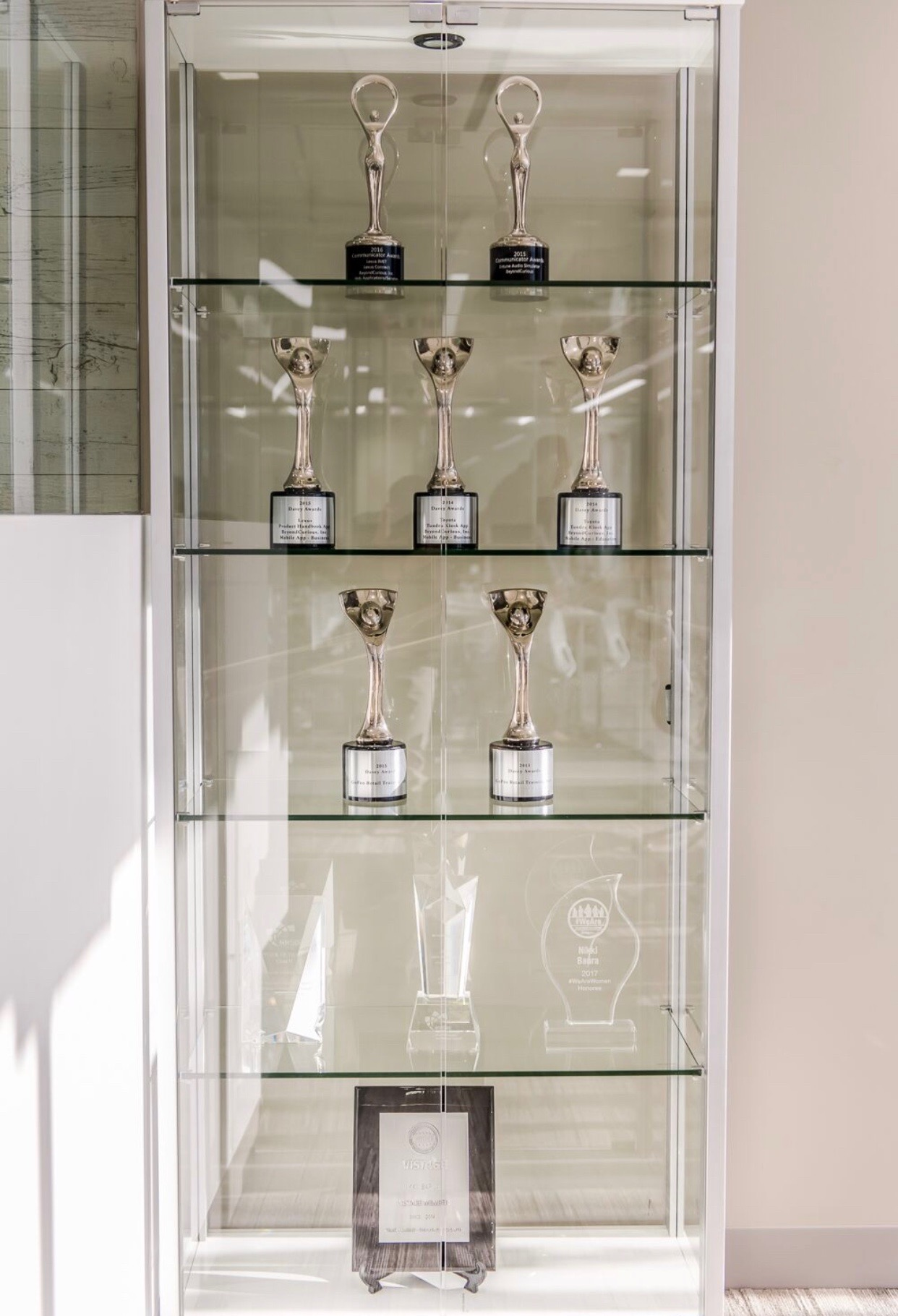An organized trophy display case for a local small business.