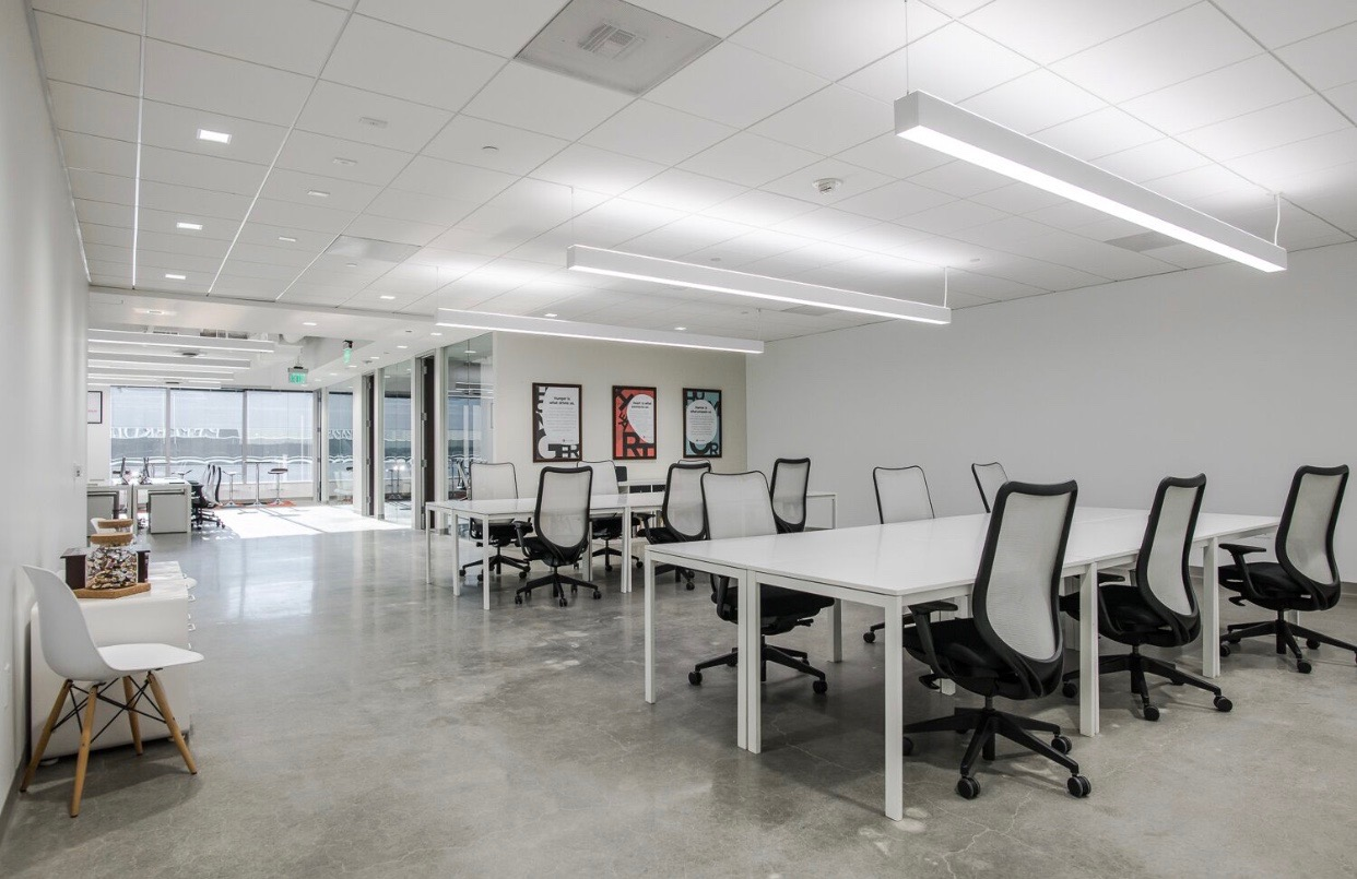 An open and minimalistic meeting room with white desks and white chairs.