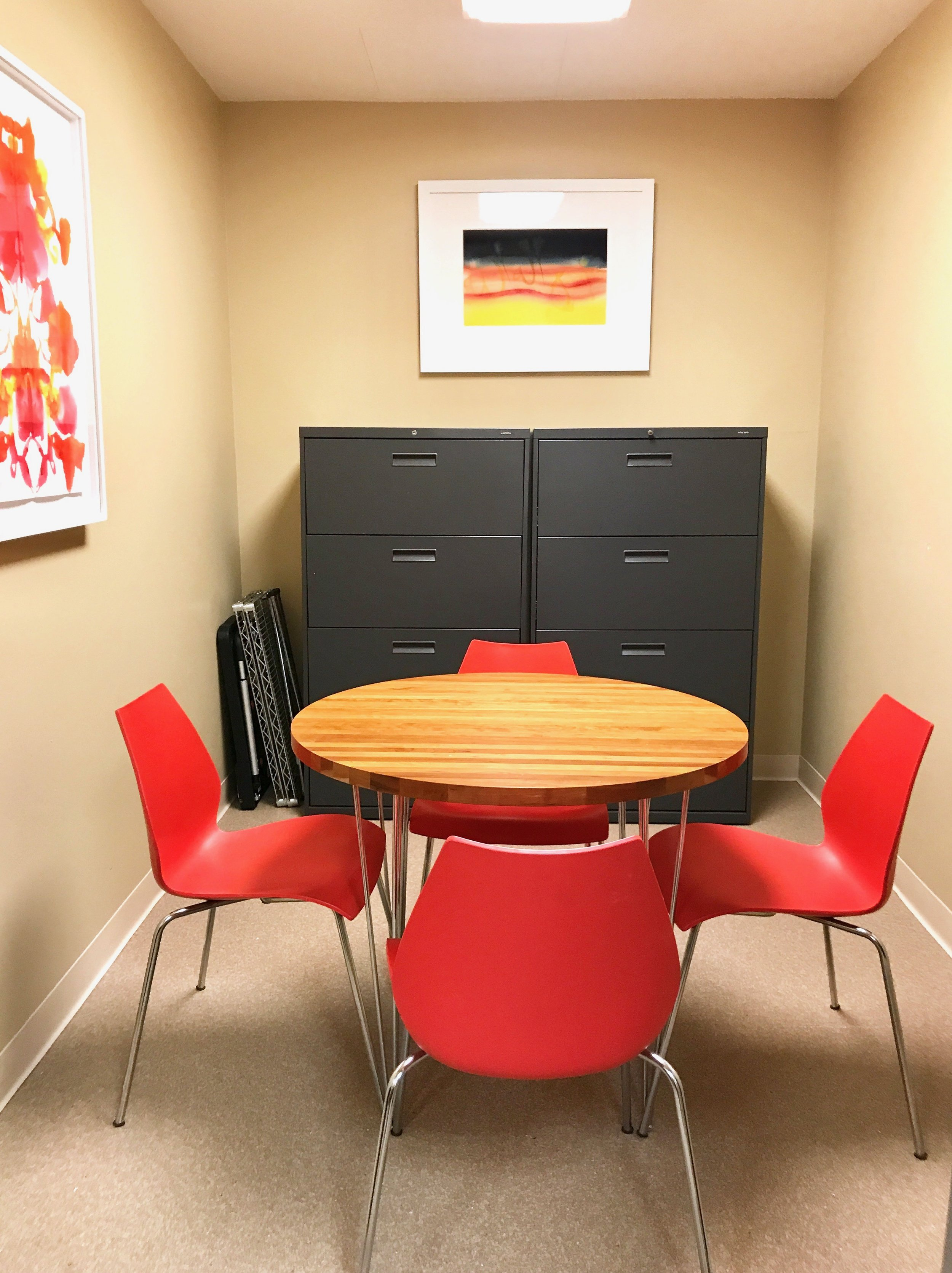 An office break room with coral accent chairs, hanging pictures, and filing cabinets.