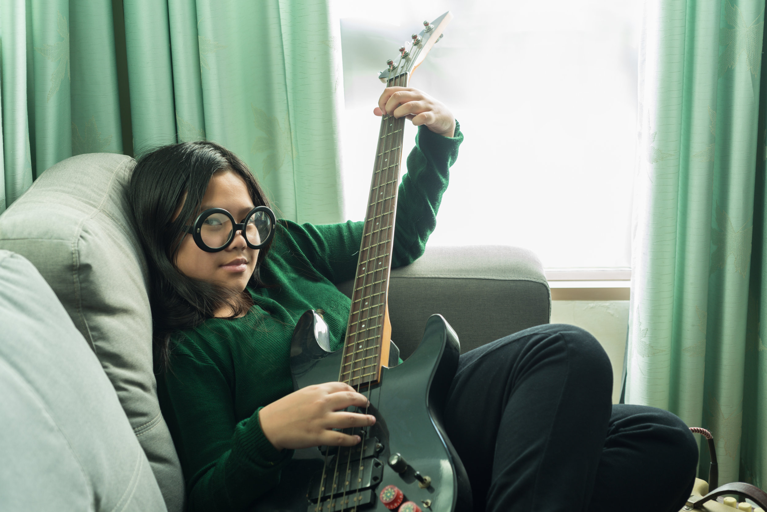 Happy smiling girl,learning to play the Bass guitar
