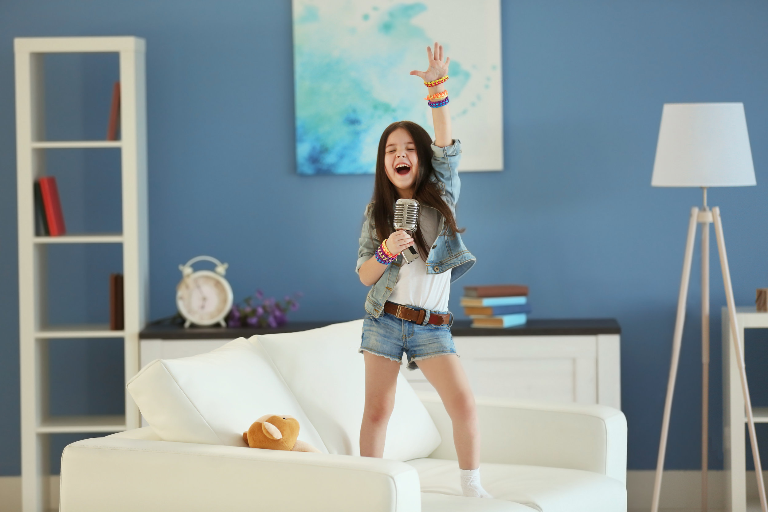 Artistic little girl singing in the room