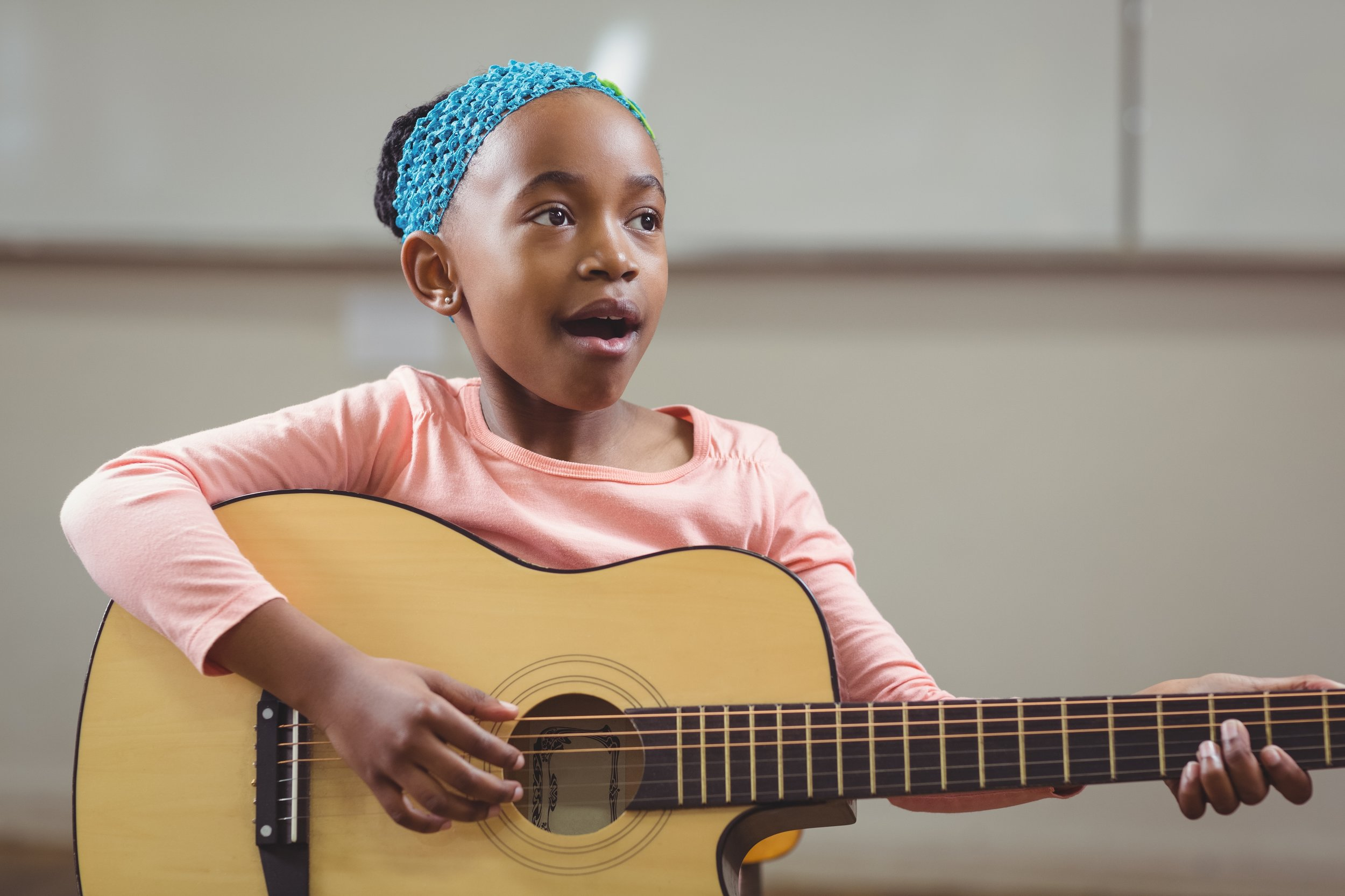 Cute pupil singing and playing guitar in a classroom