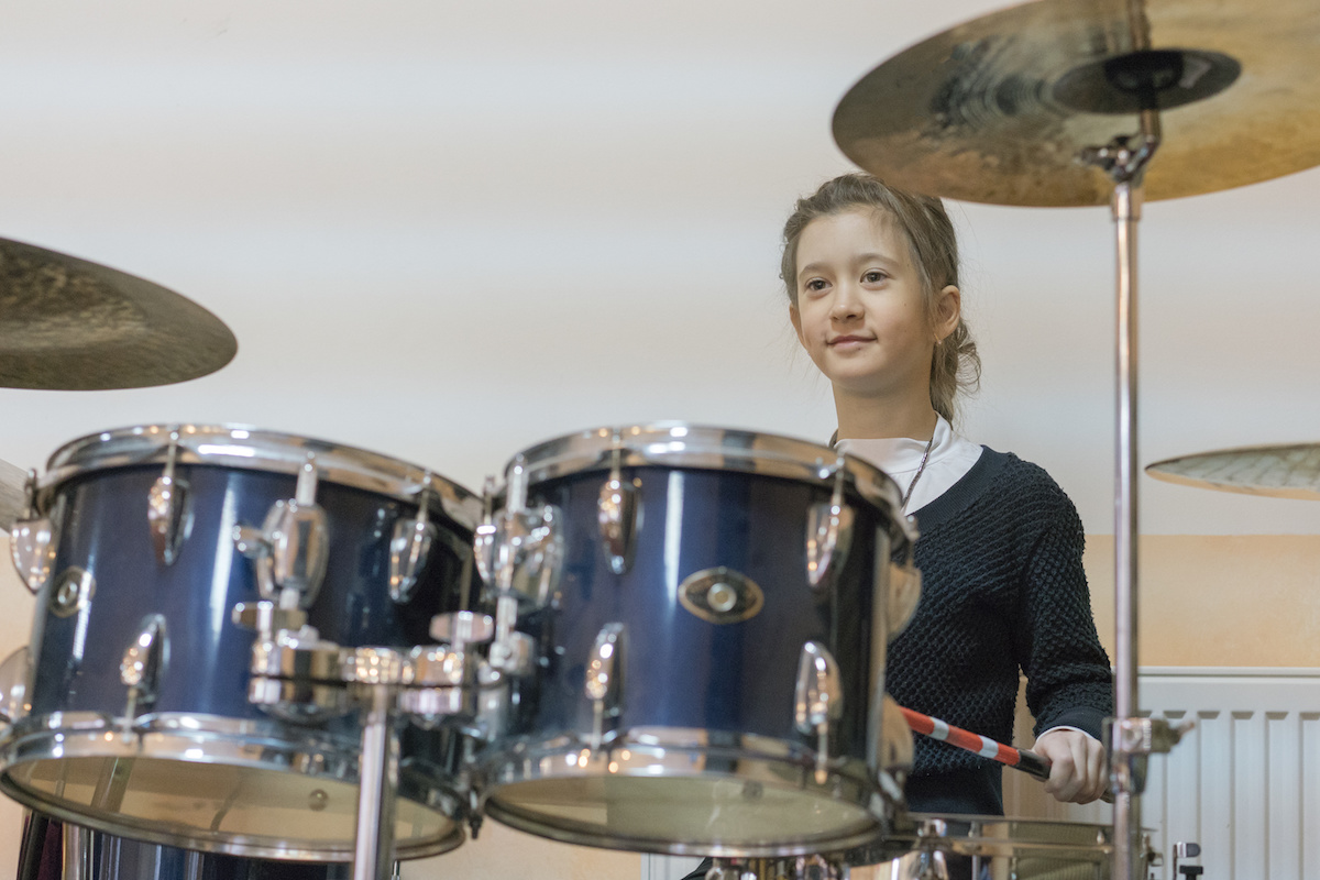 Happy girl in music therapy by playing drum kit on music room