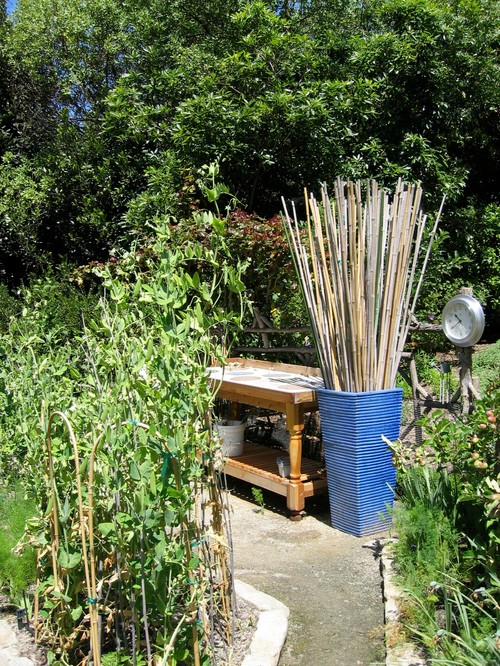 Stakes used for tomatoes and other heavy crops are attractively stored in a beautiful blue urn, which complements the Soleri tiles embedded in the potting bench.