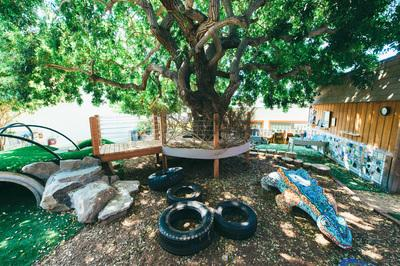 The playground is nestled under a mature Brazilian pepper tree providing shade and an undeniable connection to nature. Existing sculptural elements by local artist   Betsy K. Schulz   were integrated in the new design.