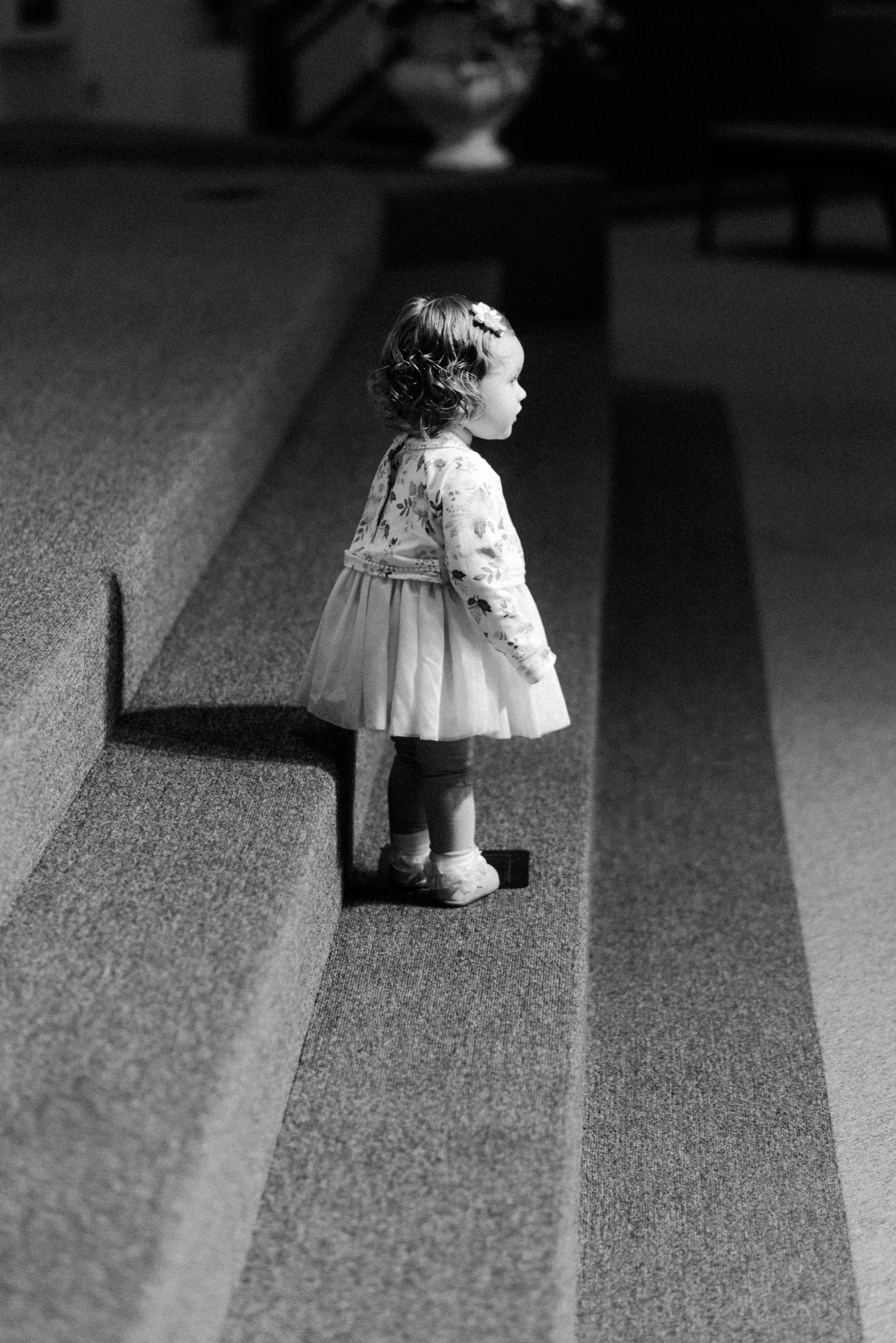 "The Richards Wedding - February 2018  Once again, the moments right before a wedding ceremony are invigorating to capture. ""You never know what you're gonna get!"" At this particular wedding, this sweet little gal kept making her way up to the front of the church to climb up and down the steps, over and over. It was super cute, and she really entertained us all while we waited for the ceremony to begin. I think what I enjoy most about this picture are the directional lines and pattern(s) that were created by the steps and the shadows casted by the lights above. The eye is drawn directly to the little girl, and her expression is inquisitive. It makes you wonder what she was thinking."