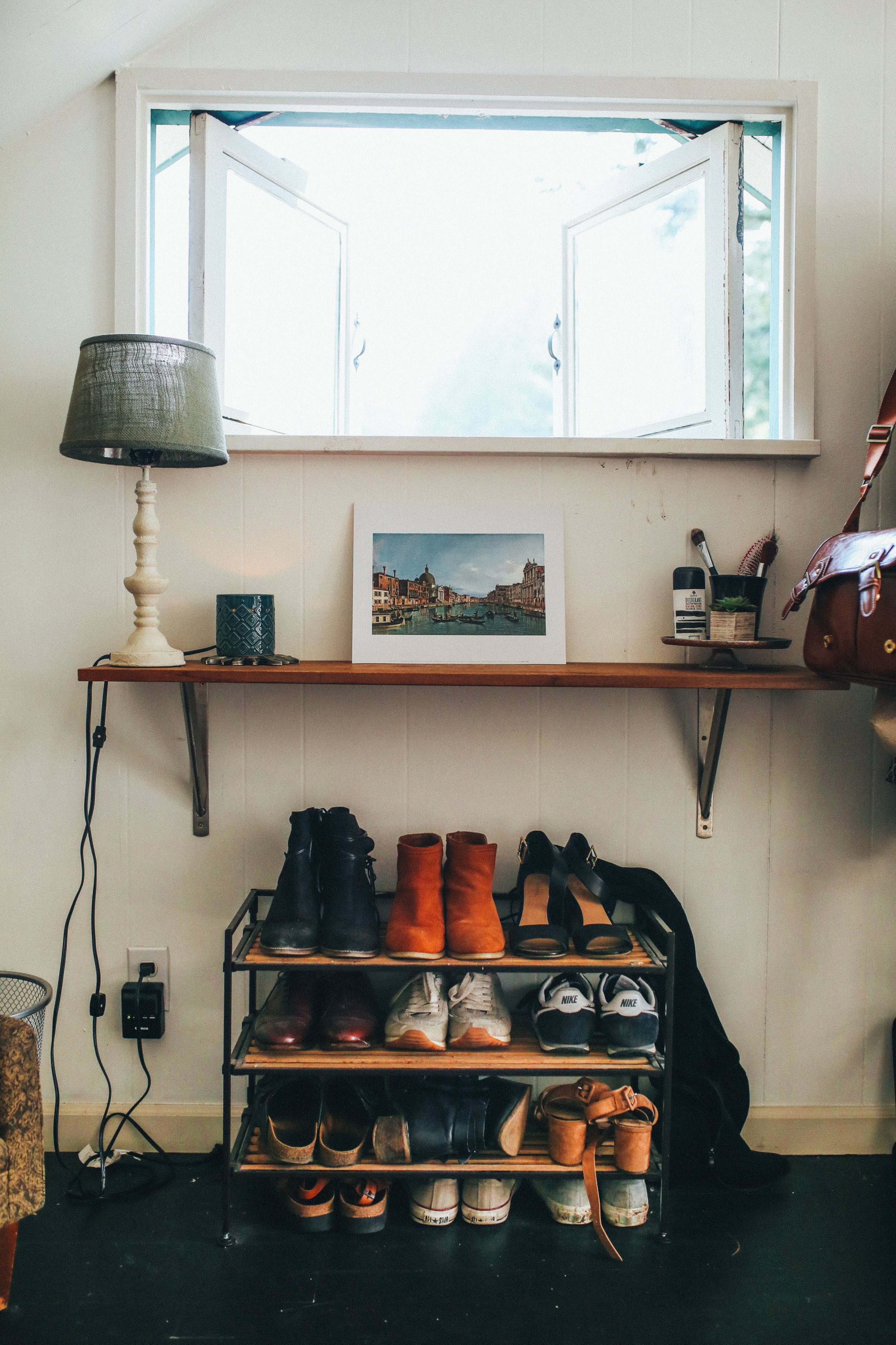 Beneath this adorable window is a shelf, and a bookshelf.
