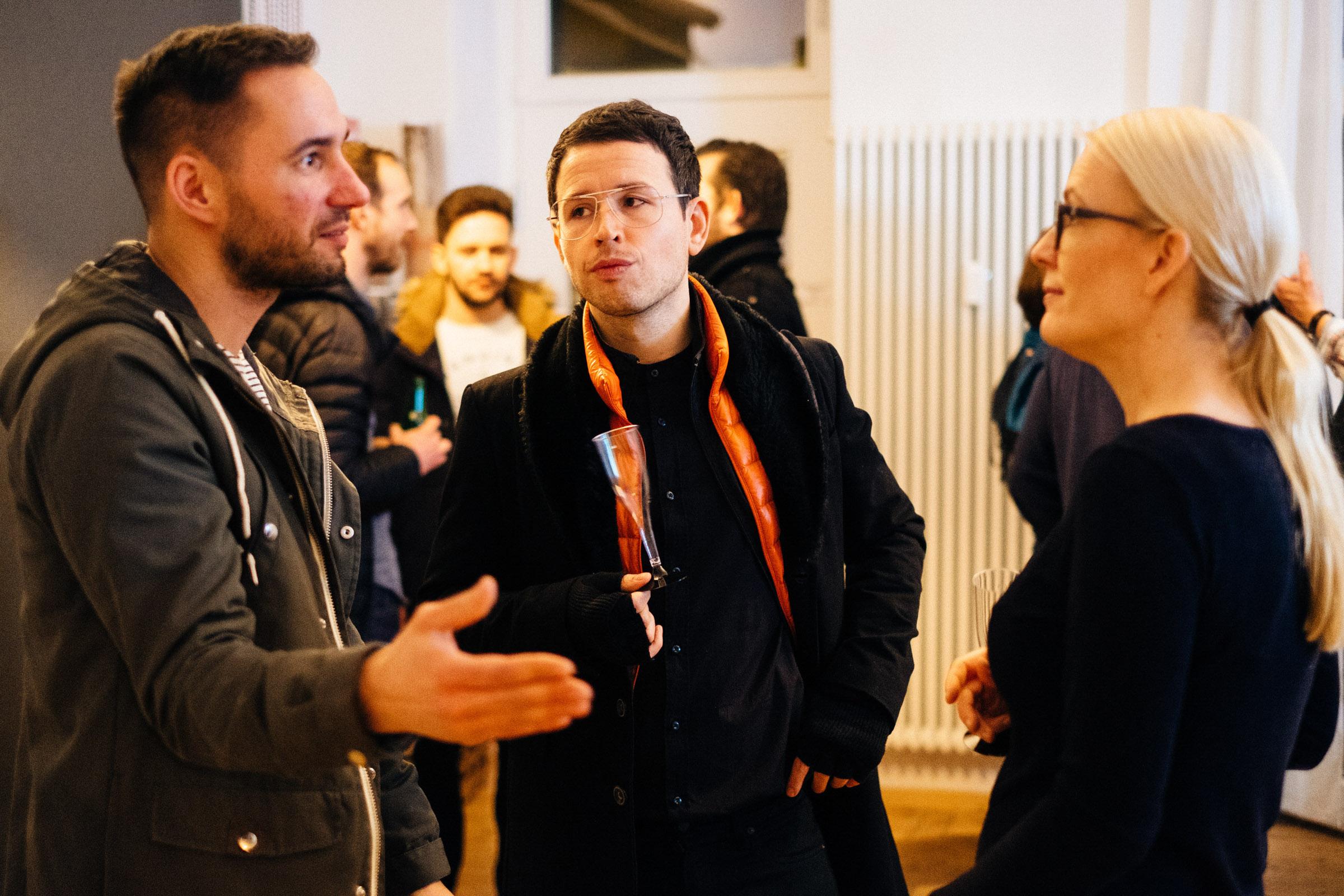 Gäste unterhalten sich auf der Eröffnungsfeier vom Fotostudio in Berlin