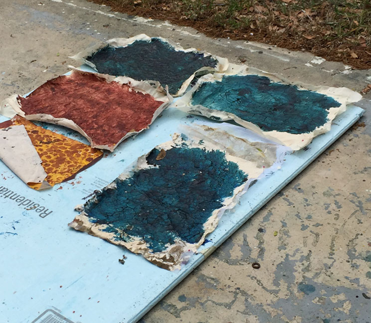 Fabric pieces with wheat paste plus paint, out in the sun to dry.