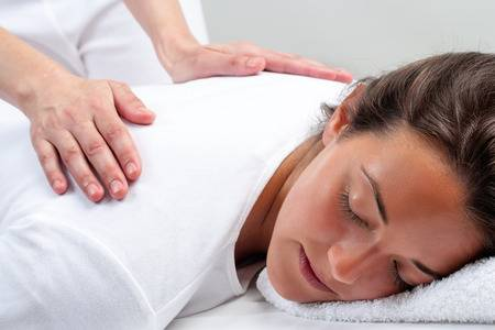 website-close-up-portrait-of-young-woman-laying-facing-head-down-therapist-doing-reiki-treatment-with-hands-.jpg