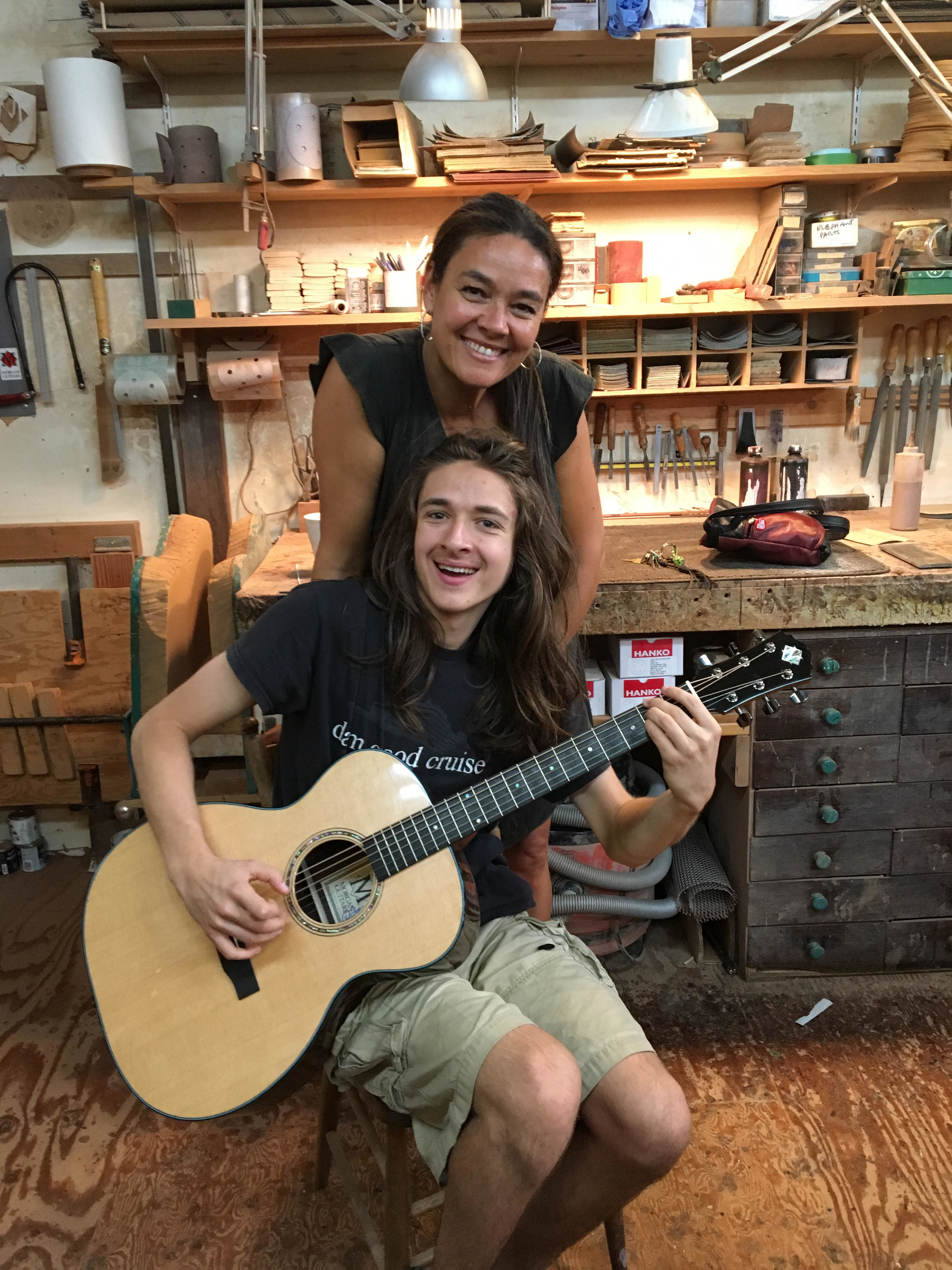 Farley and his mother, Katrina, trying out his new guitar in David's workshop.