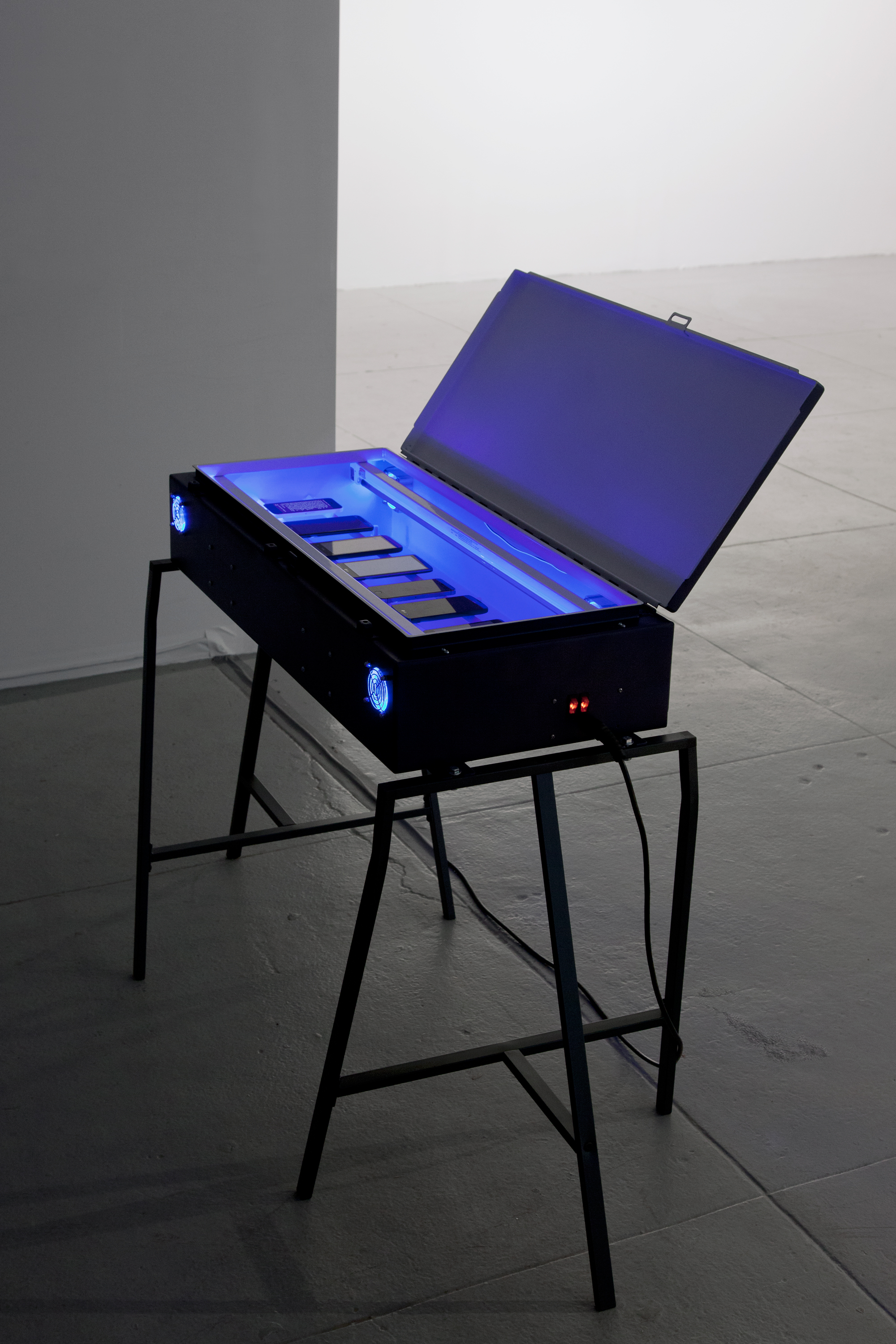 The Black Critique (Towards the Wild Beyond),  2017 Steel electrical enclosure, paint, germicidal UV light bulbs, case fans, USB outlets, electrical wire, power cord, smartphones (Elizabeth Foundation for the Arts, NY), Photo: Martha Fleming-Ives