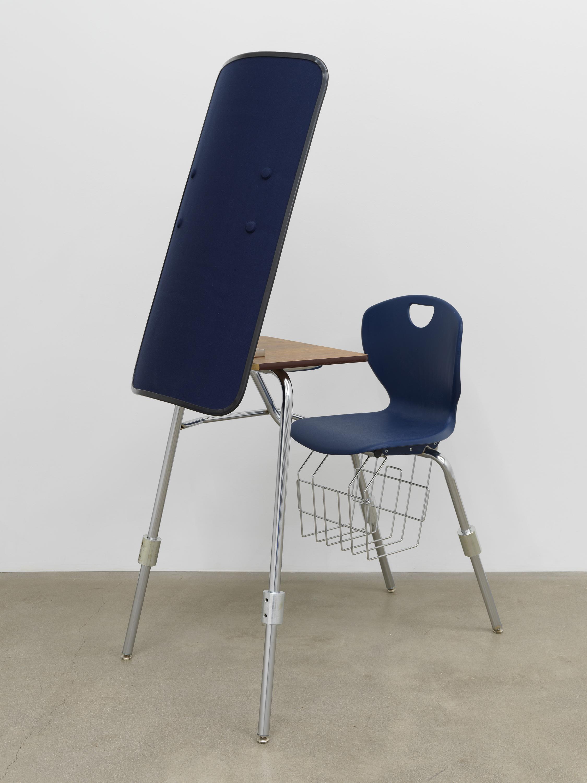 American Artist  I'm Blue, 1 , 2019, school desk, hardware, ballistic shield, navy blue fabric, books, 66 x 24 x 35 in (167.6 x 61 x 88.9 cm)