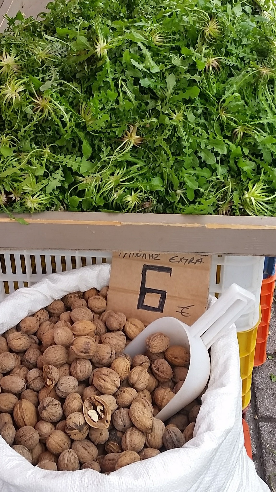 Wild foraged greens and local walnuts sold by the road in Greece