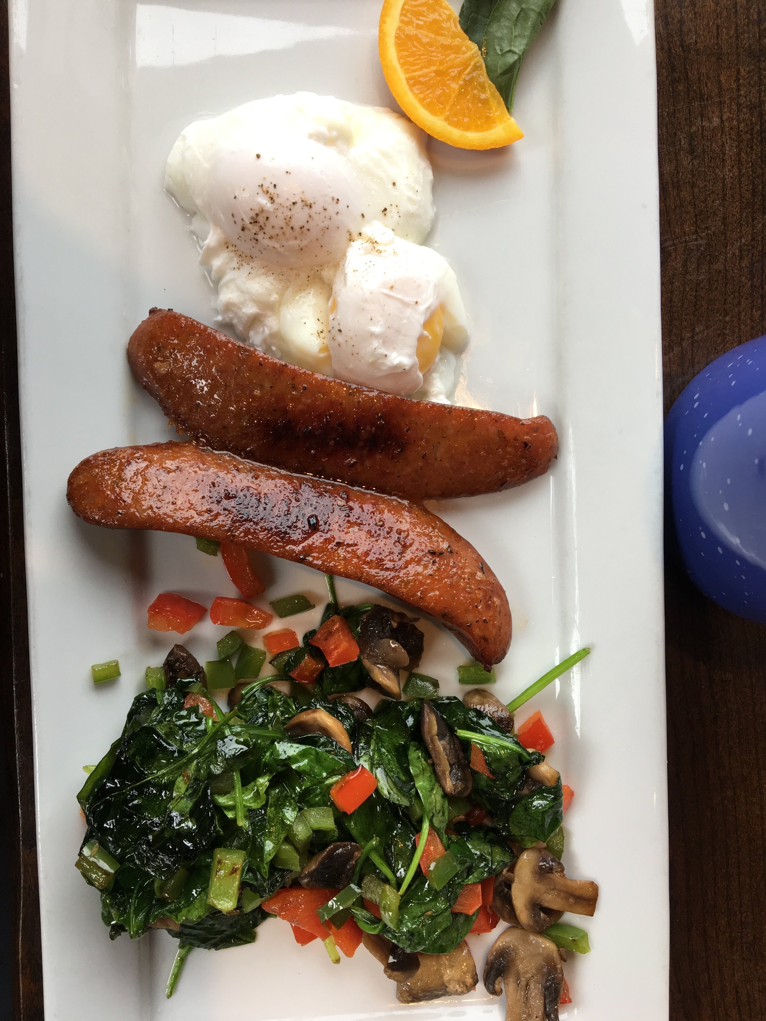 Sauteed spinach with mushrooms and bell pepper, chicken sausage, and poached eggs.