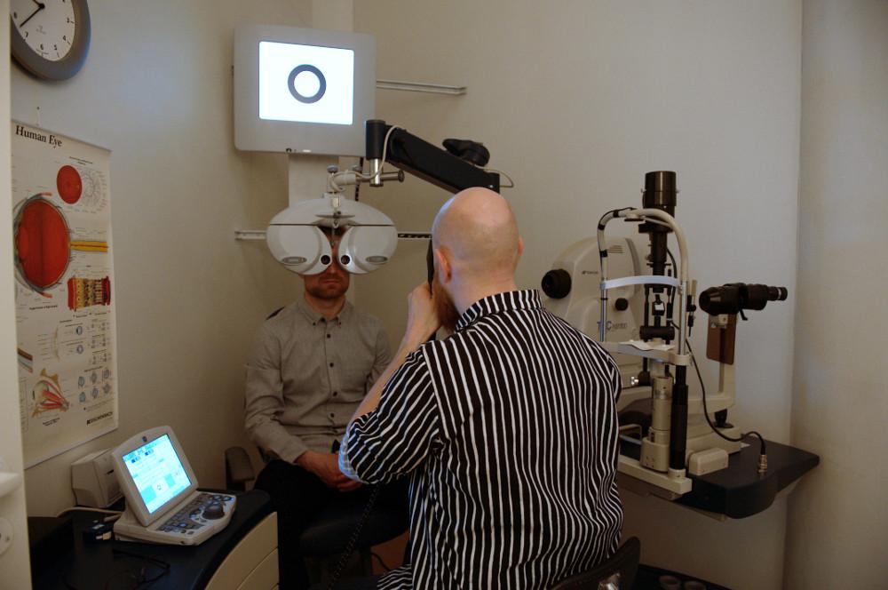 Kristian tutkii Henrin silmiä skiaskoopilla (retinoskooppi)