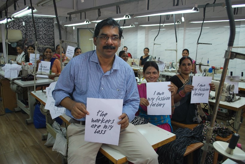 Johny Joseph, Director of Creative Handicrafts, a Fair Trade Enterprise based in Mumbai, India, holds a placard alongside garment workers in his factory. Credit: WFTO