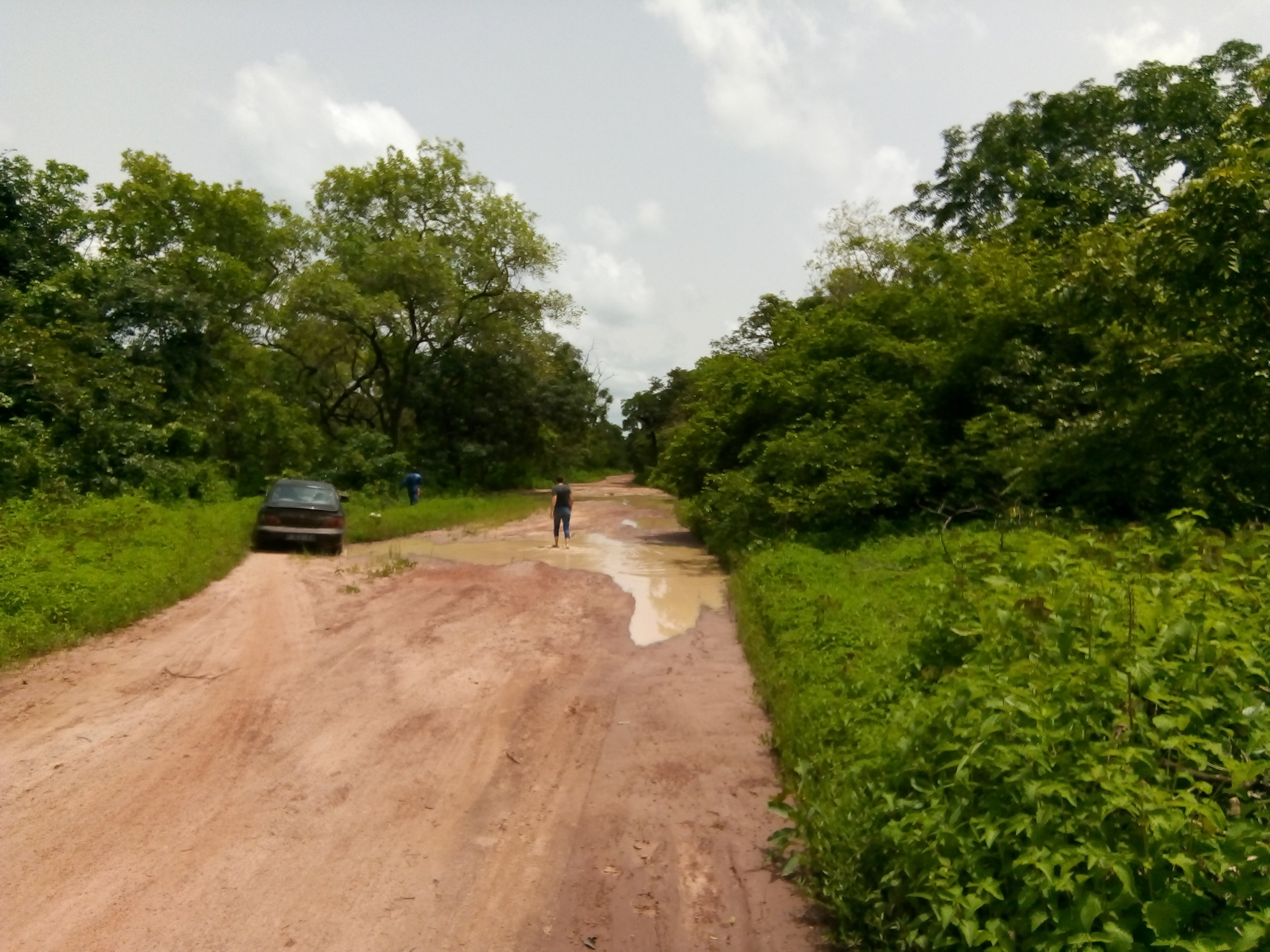 - This photo gives an impression of the condition of the roads in this region: Pierre can be seen wading through a pool of water on the road to check its depth before attempting to drive his vehicle through. Credit: Baobab des Saveurs