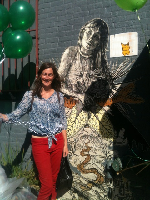 Arts Gowanus Director, Abby Subak, poses in front of the wheatpaste installation by street artist Swoon in honor of Gowanus Open Studios 2013.