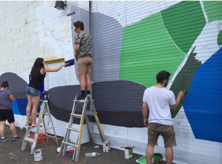 "Volunteers work with artists Julia Whitney Barnes and Ruth Hofheimer to paint the mural, ""Gowanus: Industry & Ecology"" (2015)."