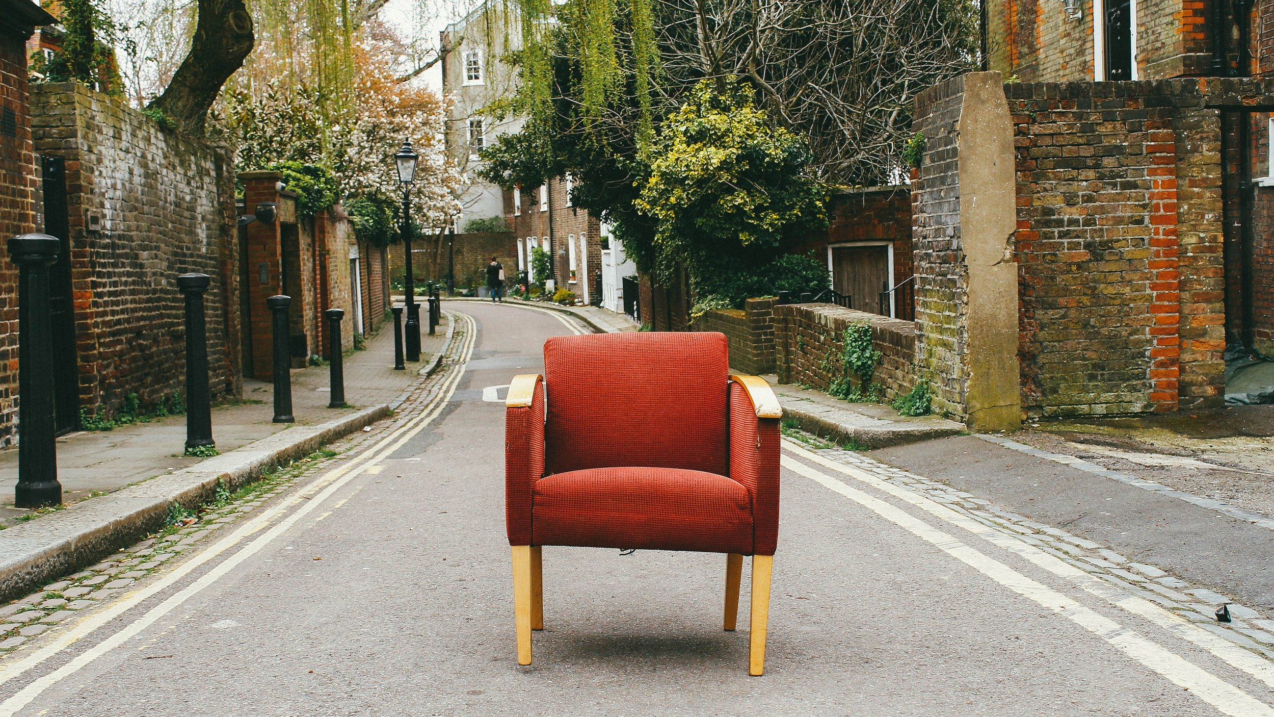 A red chair in the middle of a road