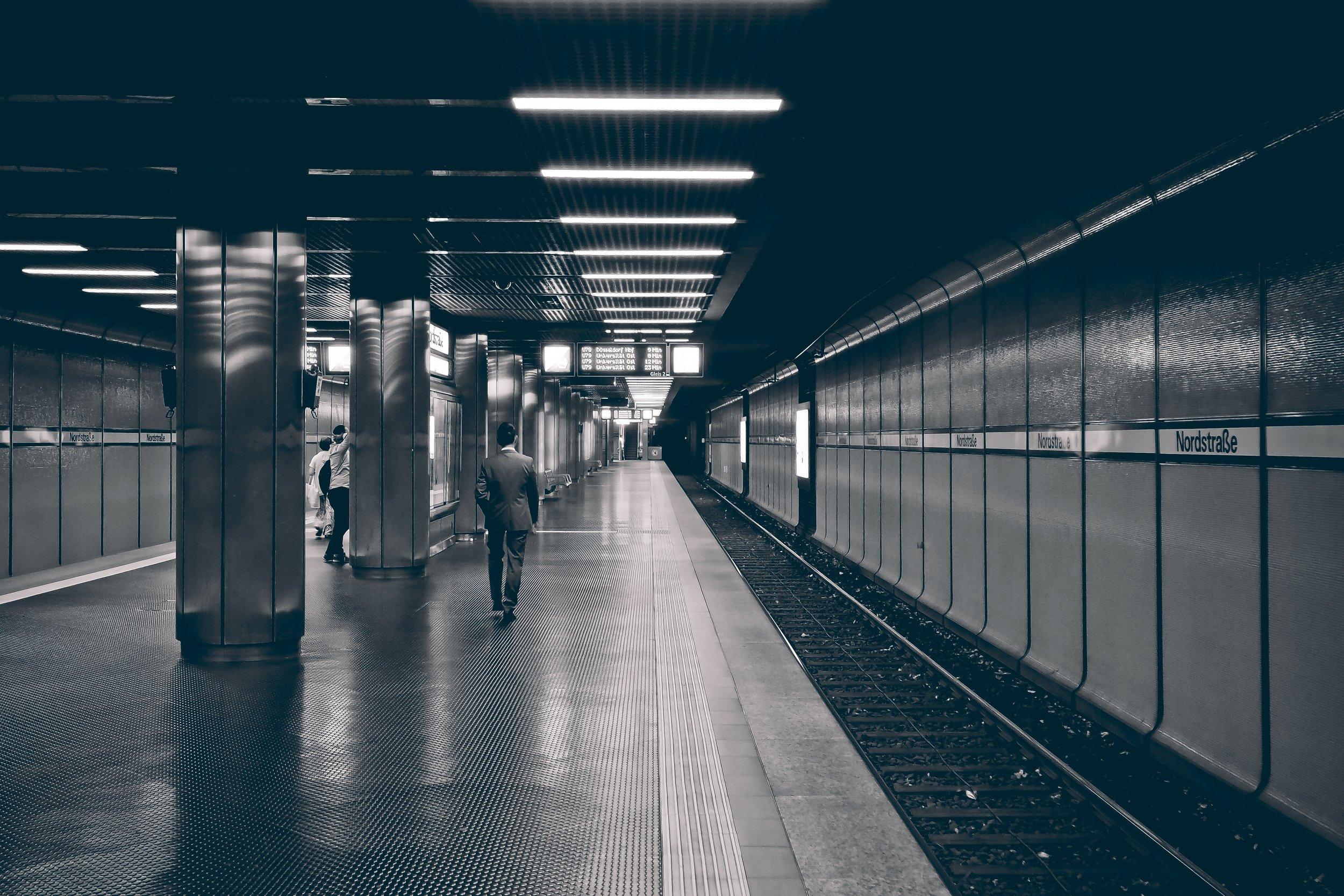 Man on train platform black and white