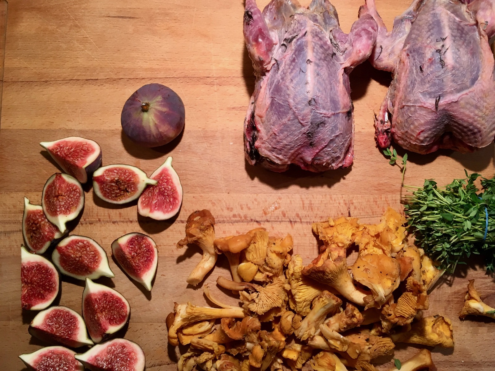Flatlay chopping board of ingredients: Grouse, Figs, Girolles, Thyme