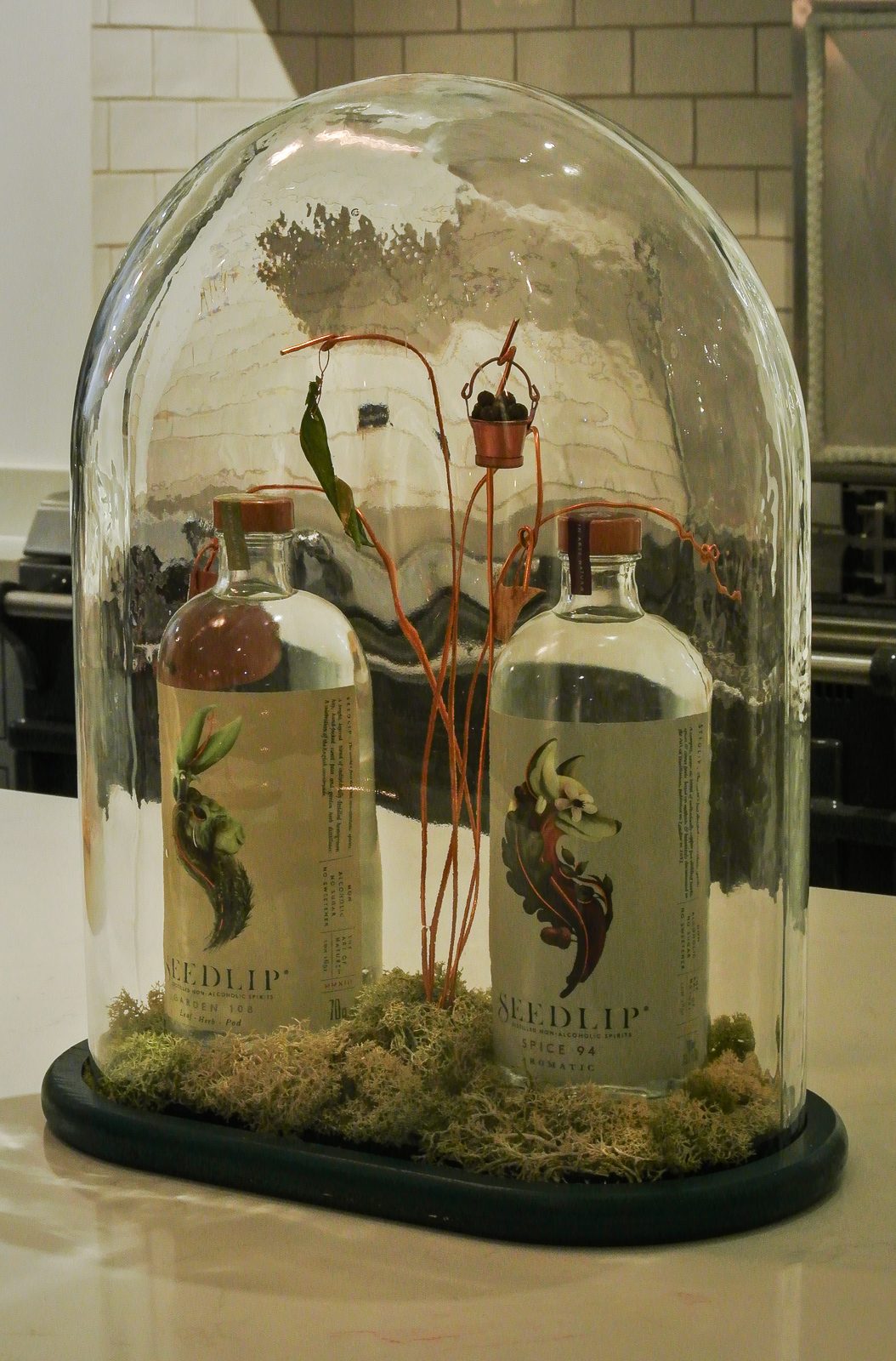 Two Seedlip bottles in a terranium - garden 108 and spice 94
