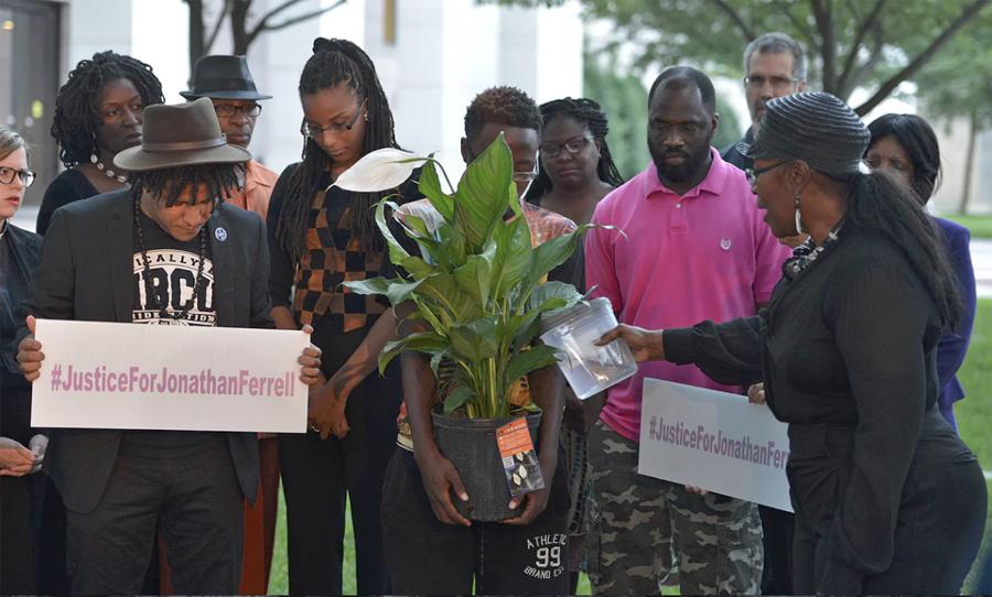 People participate in a memorial service outside the Mecklenburg County Courthouse, where the trial of Charlotte-Mecklenburg police officer Randall Kerrick is taking place, on 10 August. Photograph: Davie Hinshaw/AP
