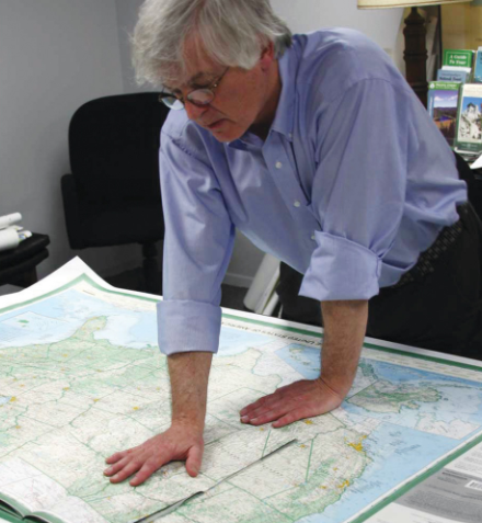 Dave Imus at a work table with the Essential Geography of the United States of America.Imus Geographics