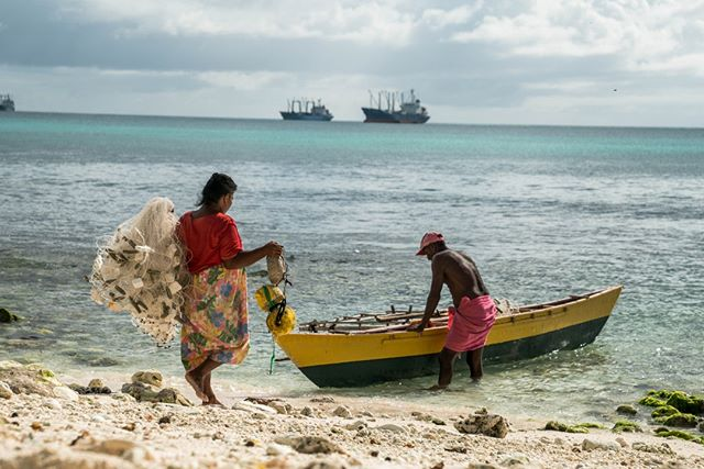 Kiribati locals. A wife helps her husband load up his fishing boat before he departs to the sea.