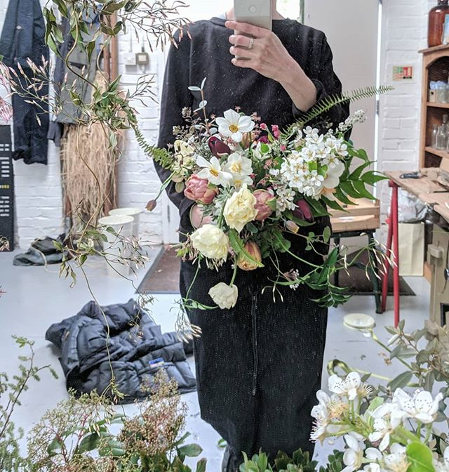 Bouquet work in progress for Julia who married Corrina in central London yesterday afternoon 💚 I did attempt an artful finished shot using a grubby linen apron artfully swathed  but this photo - taken while trying to get those pesky fern leaves to behave - perhaps captures the process more accurately. I'm a messy worker and our tiny workshop gets more and more chaotic as the flowers progress.  The jasmine quietly dying top left was unintentionally hanging there...evidence to the fact I can't bear to ever throw any flower away even once we've reached the green gungey stem stage 🤢 I *did* have a good tidy up before heading off on holiday (mainly to avoid immediate assassination at the hands of Camila on my return to London) and those ferns did behave themselves eventually 🌿Wishing J and C many years of health and happiness 🥰 I'm off up north for a holiday (albeit via @simplybyarrangement with Cam for some tips on fern wrangling on Monday and then a visit to Chatsworth 🙌) but Camila back in the (tidy) office on Tuesday 😊 have a great Sunday!