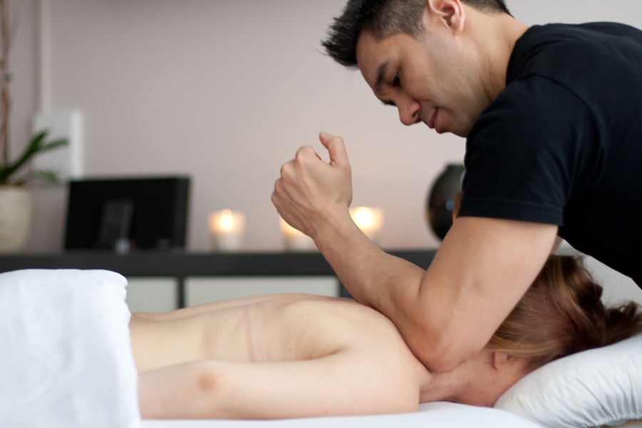 Massage therapist providing deep tissue massage on a client's shoulder.