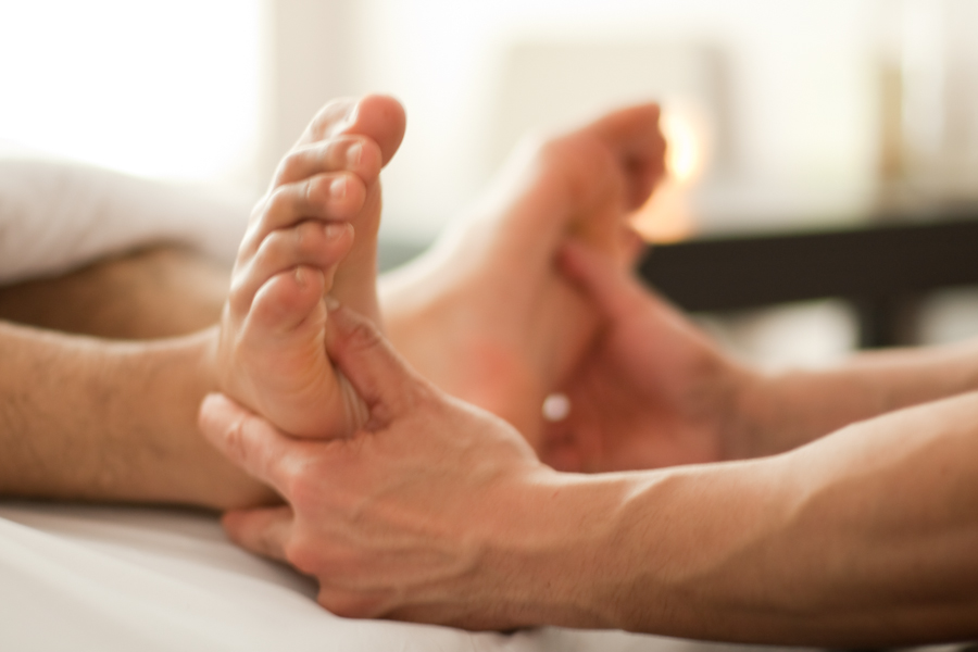Massage therapist pressing on the solar plexus reflexology points on a client's feet.