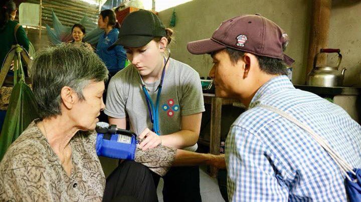 Murdoch student taking blood pressure with partient and translator, Vietnam 16-9.jpg