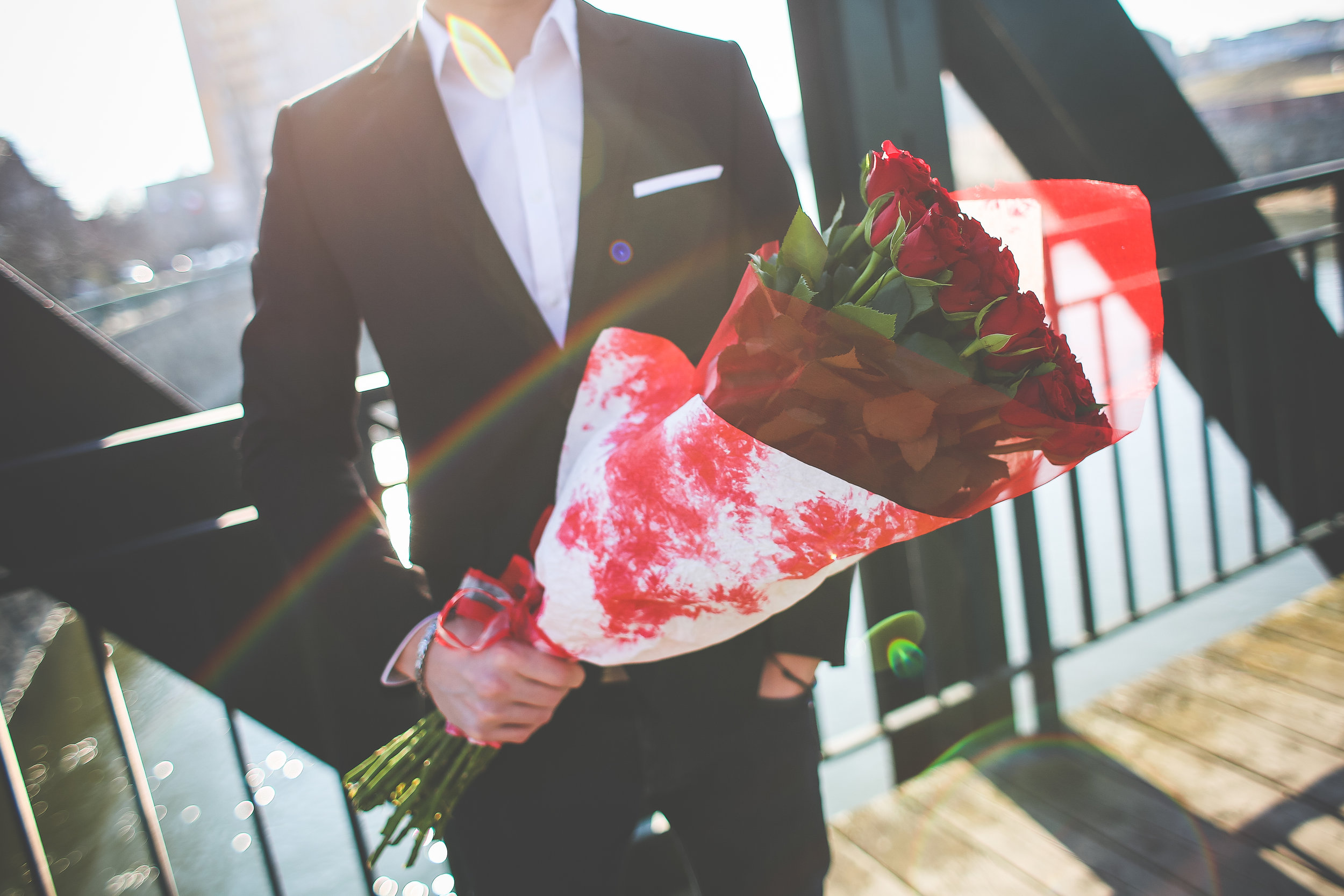 gentleman-holding-a-bouquet-of-roses-and-waiting-for-his-wife-picjumbo-com.jpg