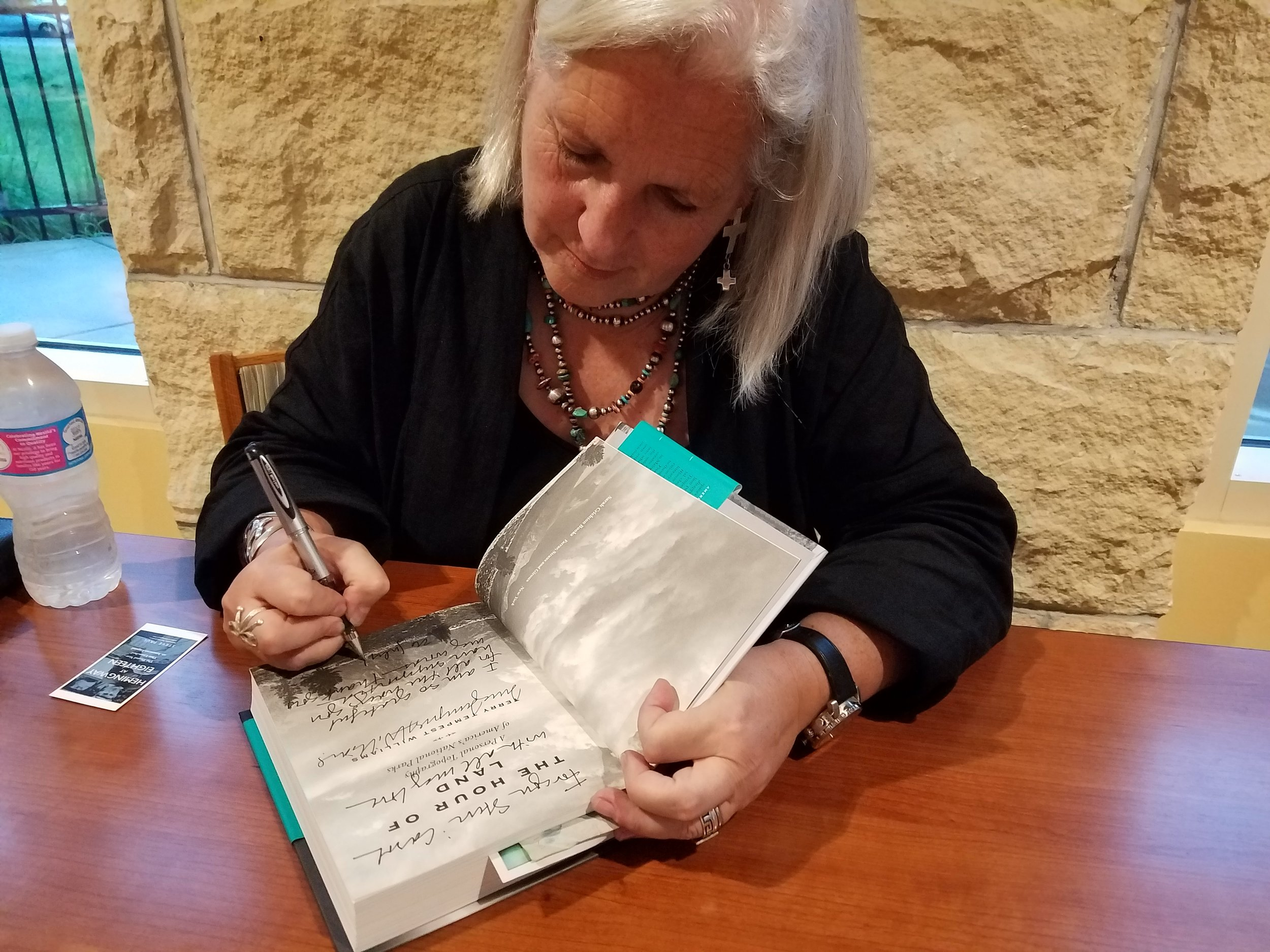 Terry Tempest Williams personalizes a copy of her latest book,  The Hour of Land  after her talk at the Woodneath Library in Kansas City.