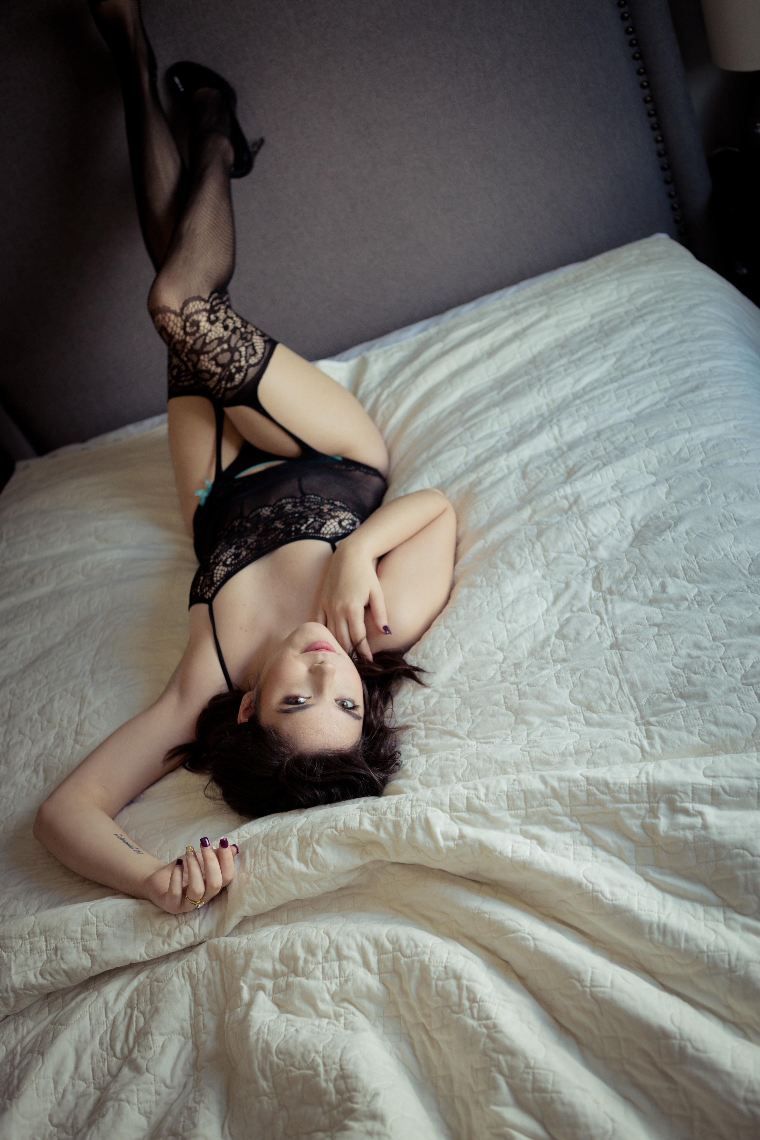 Woman in black lingerie on bed. Boudoir session in Helena, Montana by boudoir photographer Misty Boles