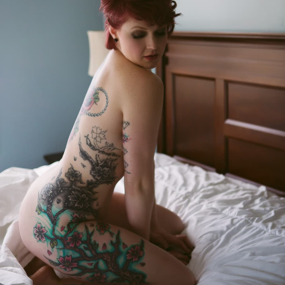 Nude woman with a large tattoo sitting on bed.  Boudoir Photo by Misty Boles Intimate Photography.