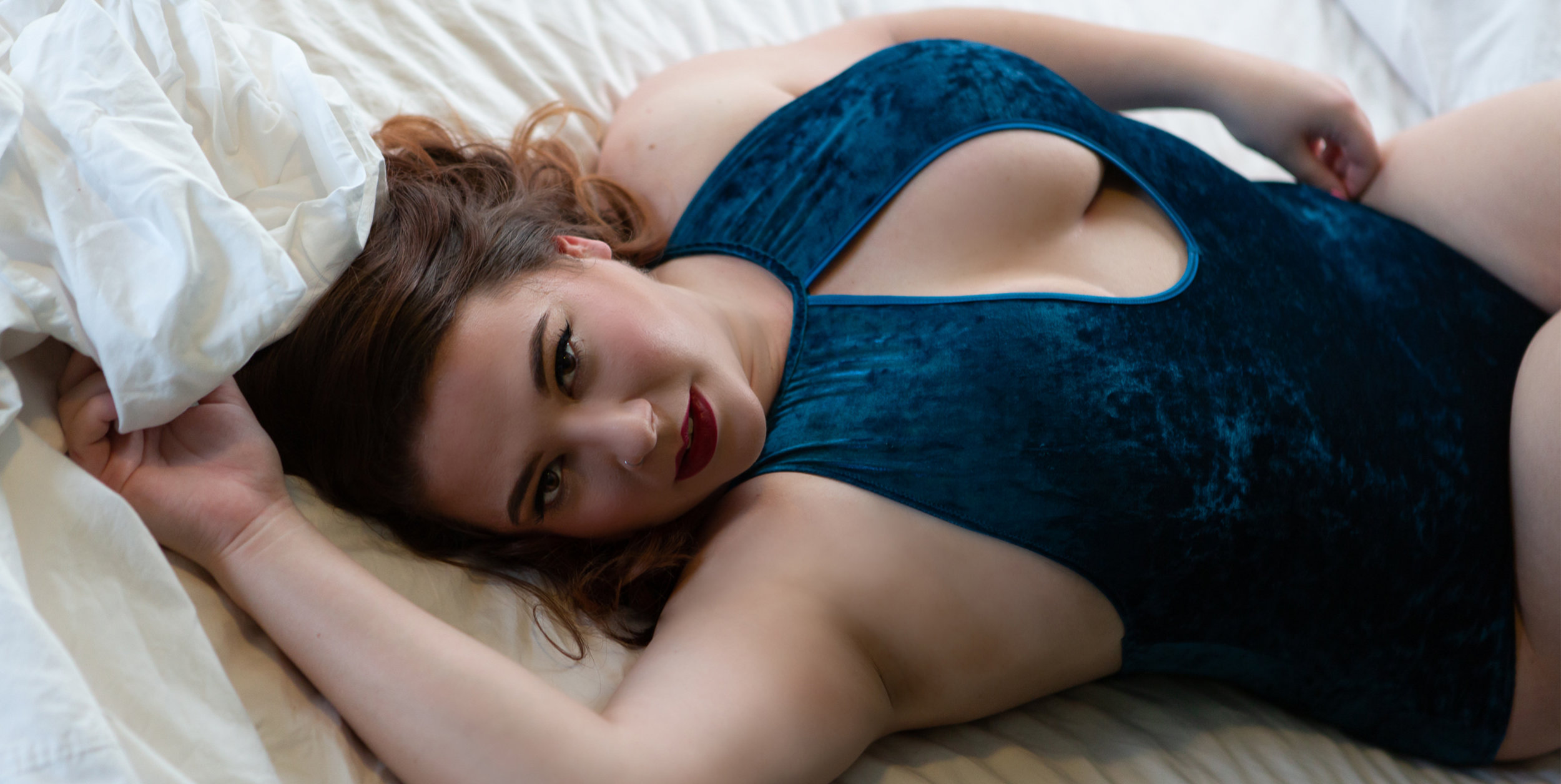 Helena Montana Boudoir by Misty Boles Intimate Photography.Curvy Woman in blue lingerie grabbing the sheets. Boudoir photo by Misty Boles Intimate Photography
