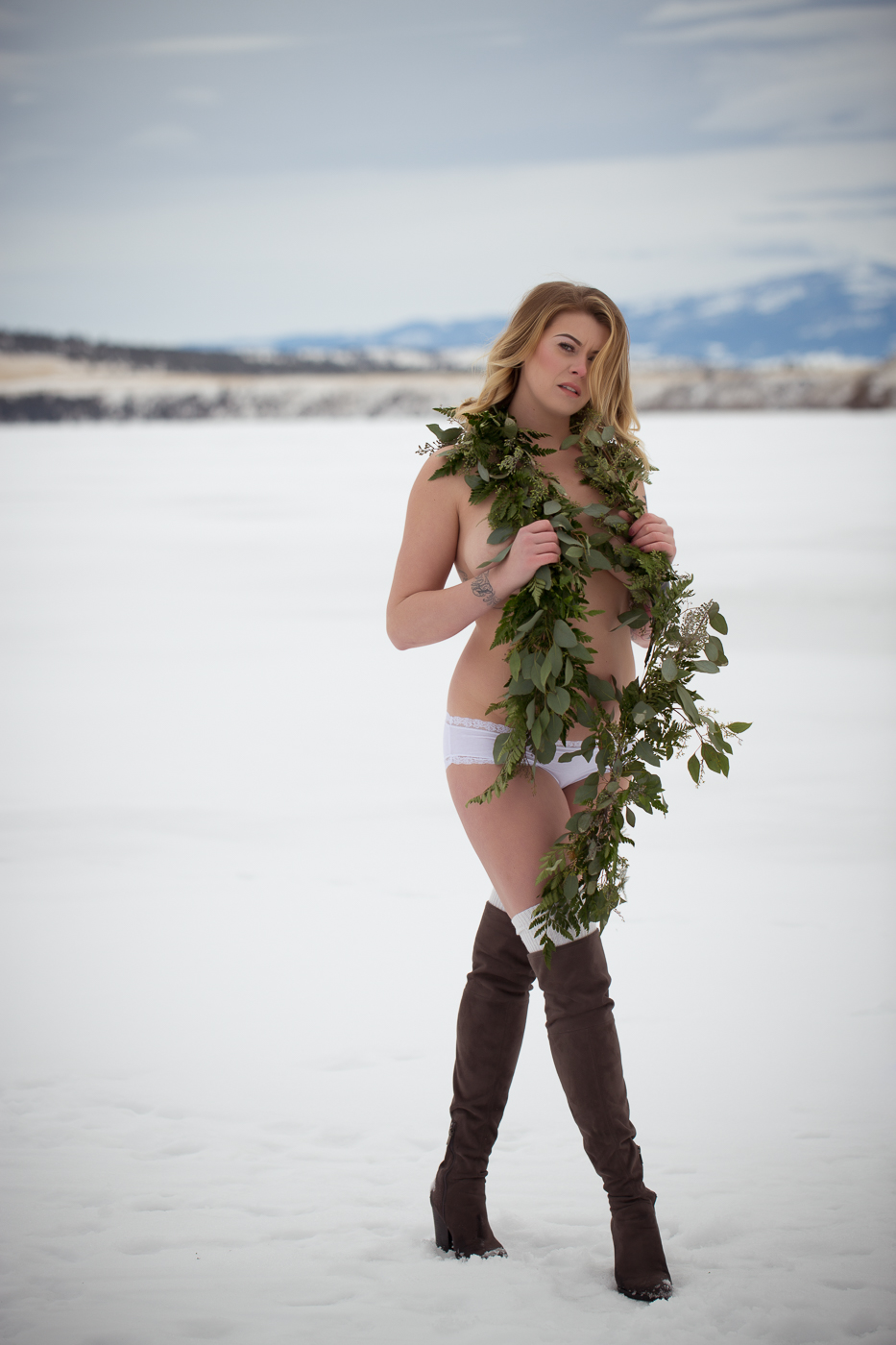 Woman on frozen lake with kick ass boots. Montana Outdoor Boudoir photo by Misty Boles Intimate Photography
