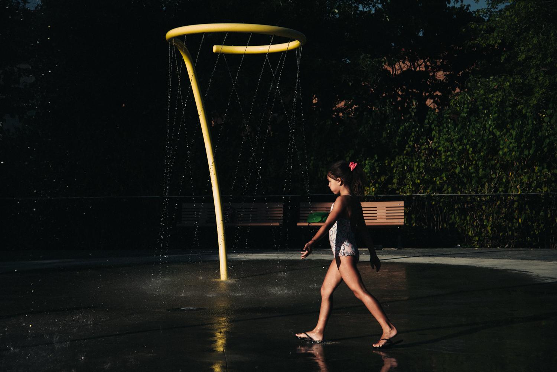 girl walking at a sprinkler pak in Montreal