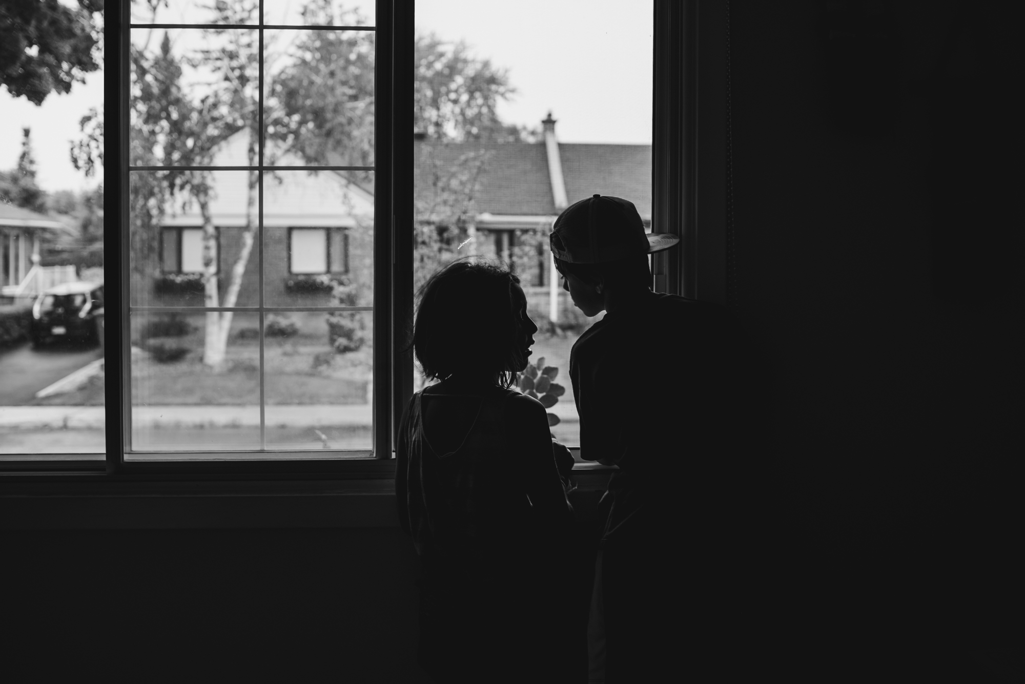 a boy and a girls looking out the window