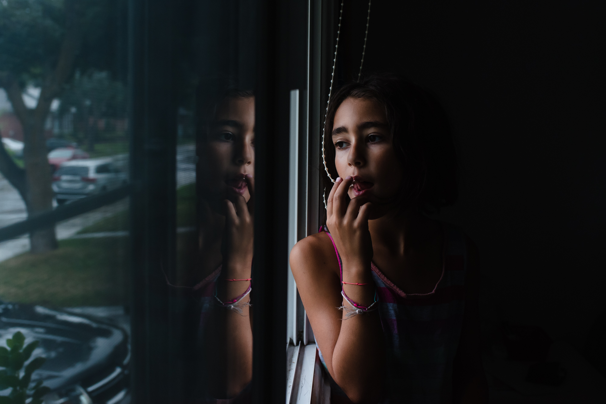girls looking out the window with her reflection in the glass