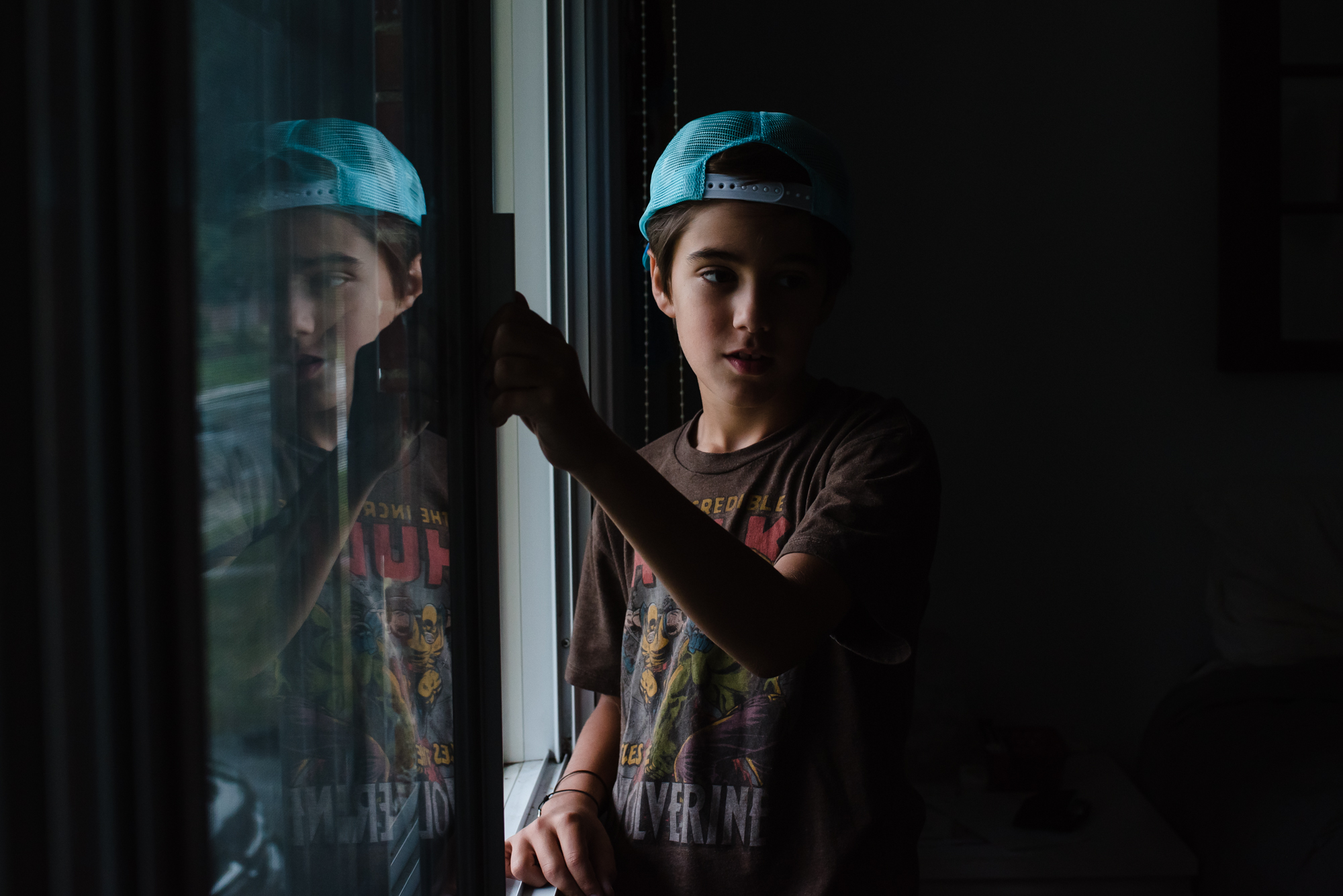 boy wearing a baseball cap opening a window with his reflection in the glass