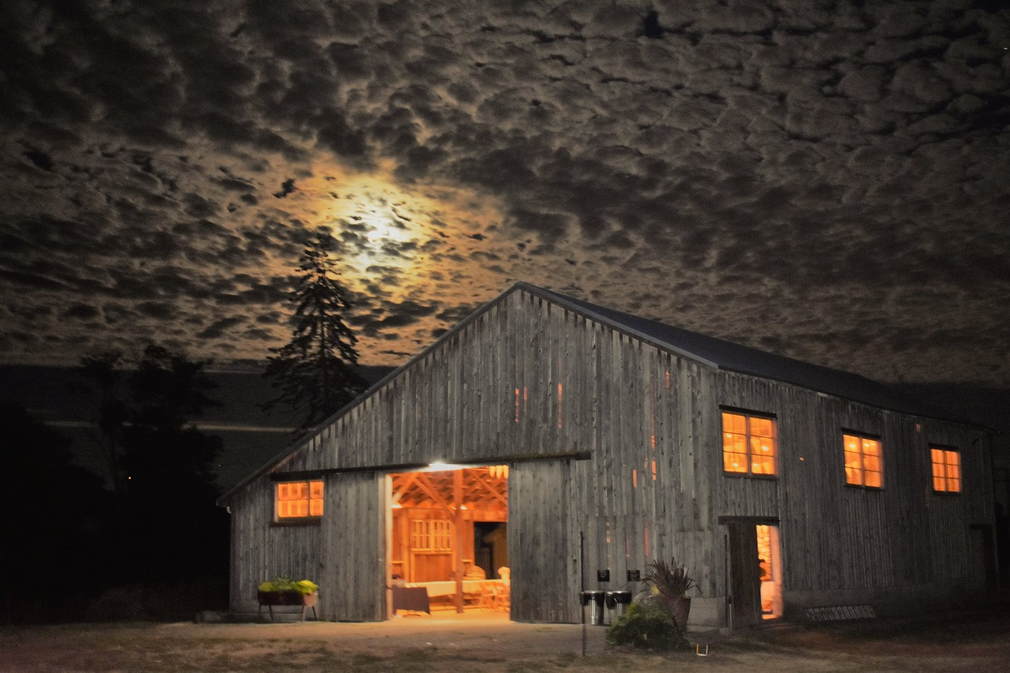 the event barn at night, a full buck moon is seen through a unique cloud covering