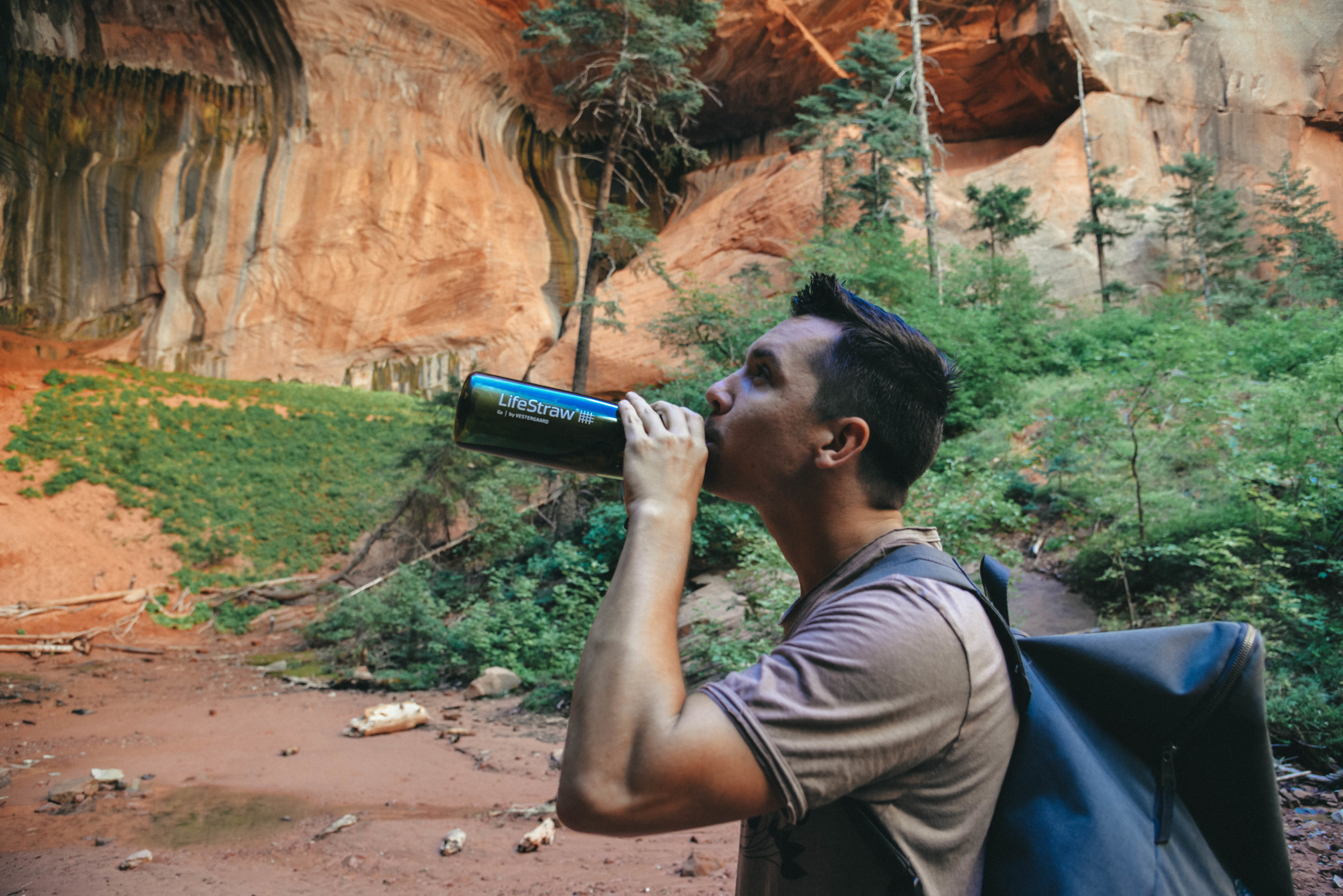 Jimmy drinking stream water from a LifeStraw at Zion National Park.