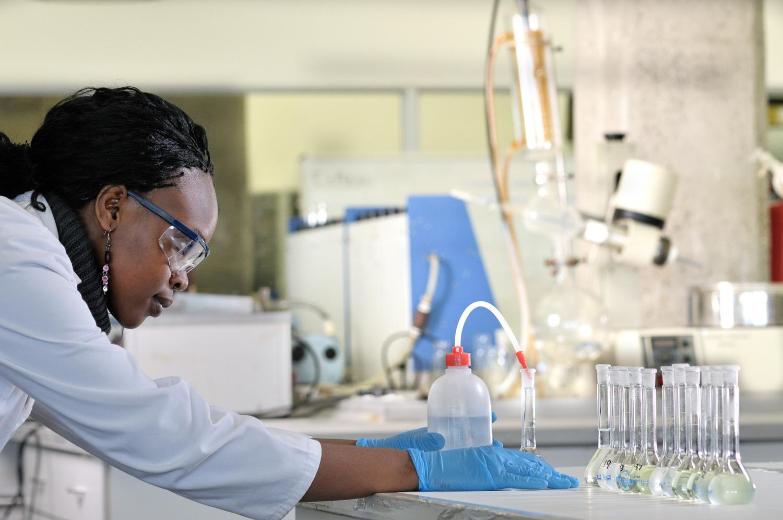 Biochemist decants fluid in flask. Image credit: Jaco Wolmarans/Getty Images